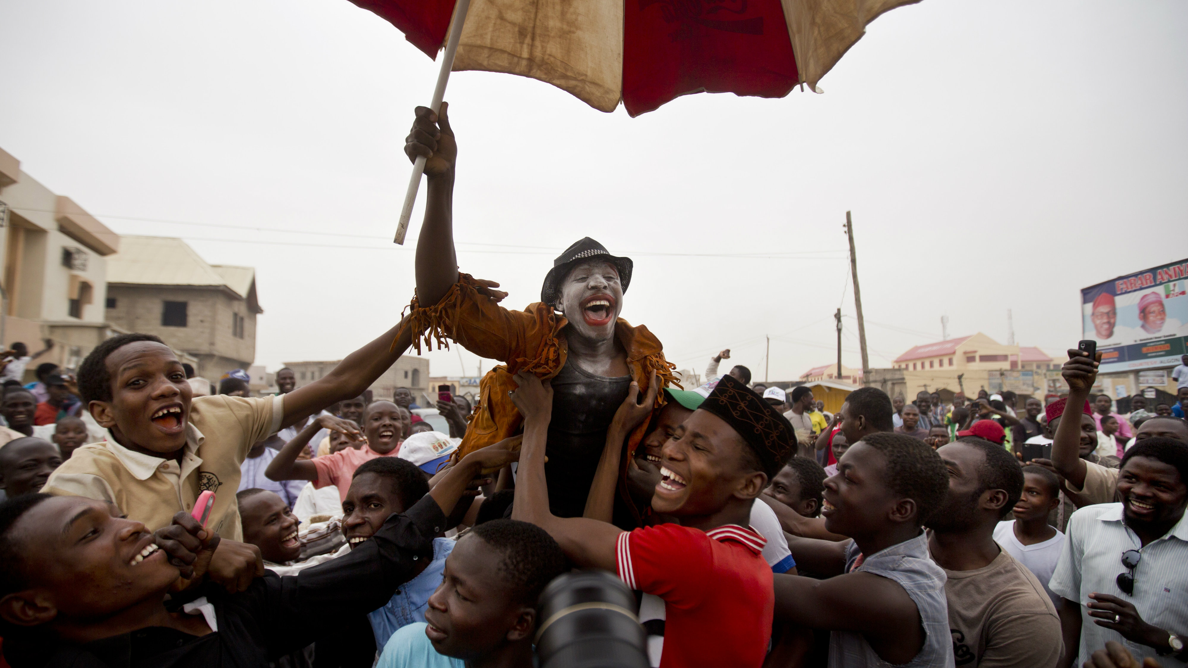 A supporter of opposition candidate Muhammadu Buhari, center, who is dressed up to represent and mock current President Goodluck Jonathan, celebrates an anticipated win for his candidate, in Kano, northern Nigeria Tuesday, March 31, 2015. Amid anger over an Islamist insurgency that has claimed thousands of lives, Nigerians returned 72-year-old former military dictator Muhammadu Buhari to power Tuesday in the most hotly contested election in the country's history.