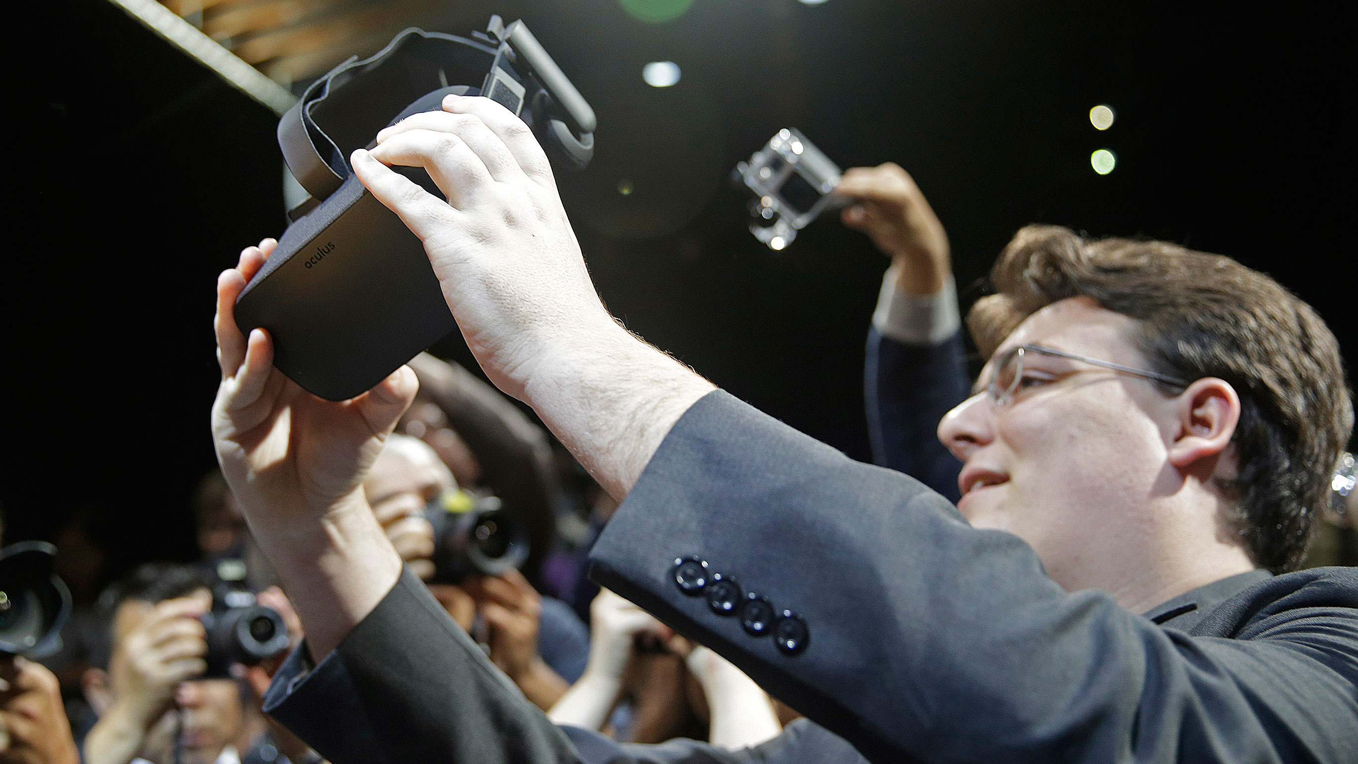 Oculus founder Palmer Luckey holds up the new Oculus Rift virtual reality headset for photographers following a news conference Thursday, June 11, 2015, in San Francisco.(AP Photo/Eric Risberg)