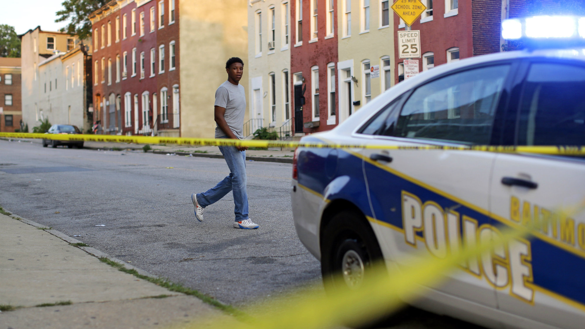 In this July 30, 2015 picture, a man walks past a corner where a victim of a shooting was discovered in Baltimore. Murders are spiking again in Baltimore, three months after Freddie Gray's death in police custody sparked riots.
