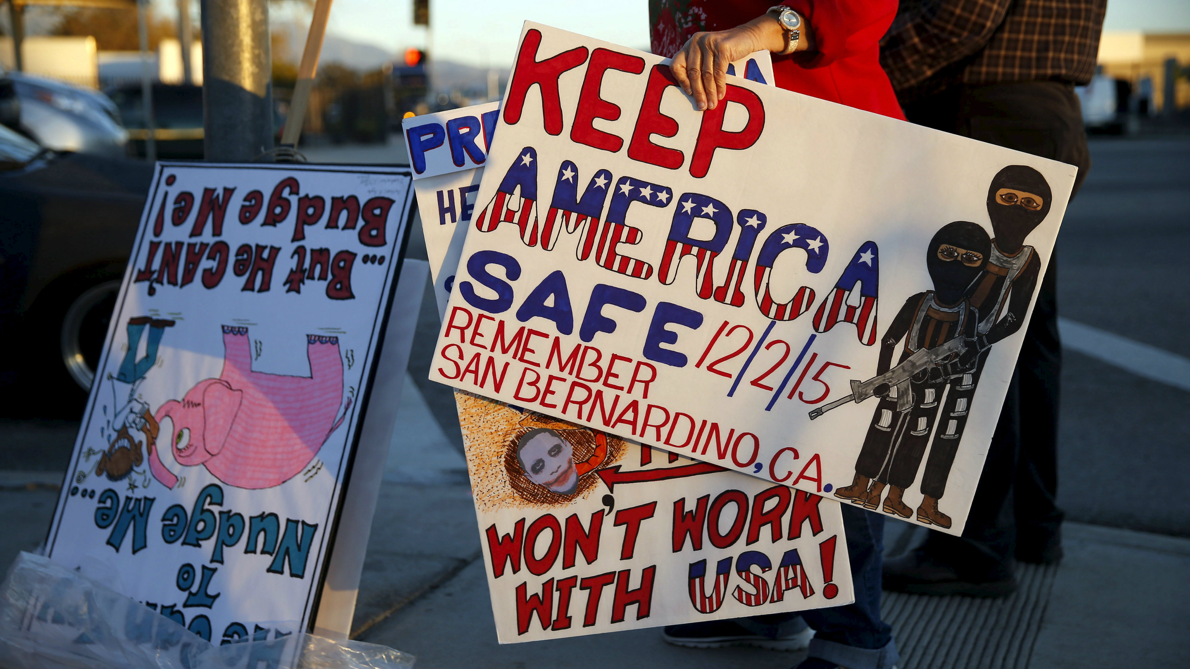 Deann D'Lean holds signs as she protests against ISIS and President Obama across from a makeshift memorial for victims of the San Bernardino shooting, ahead of President Obama's visit with the victims' families in San Bernardino, California on December 18, 2015. REUTERS/Patrick T. Fallon