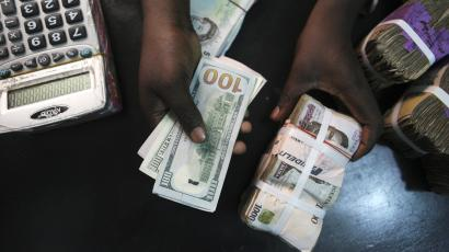 A trader changes dollars for Naira at a currency exchange store in Lagos, February 12, 2015.
