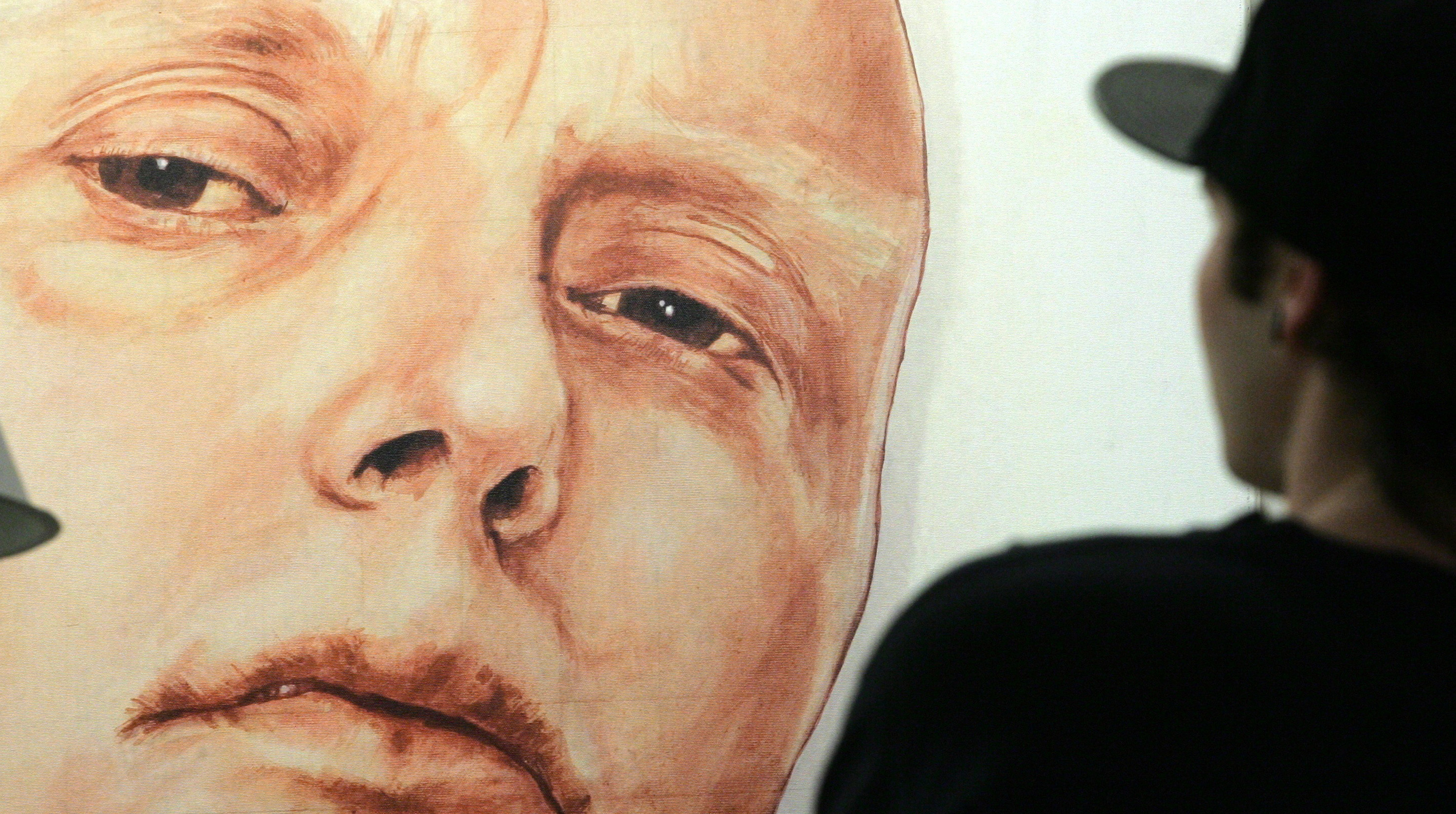 A man looks at a portrait of ex-spy Andrei Litvinenko in a gallery in Moscow