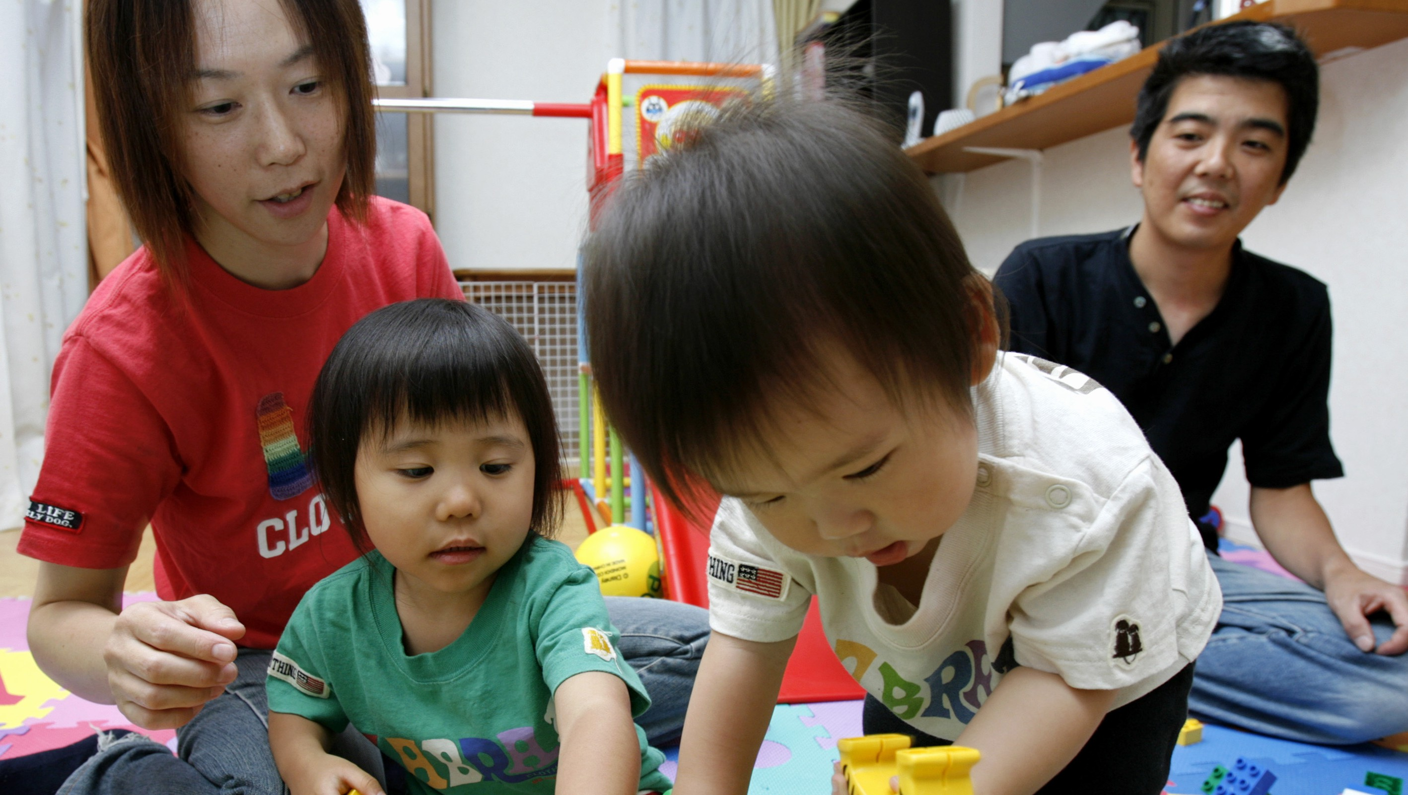 "Tomoyo Suzuki and her husband play with their adopted children at their home near Tokyo July 4, 2007. When a newborn baby girl was left in Japan's controversial ""baby hatch"" last week, the child's life may have been saved, but her chances of finding new parents were slim due to a cultural aversion to adoption in Japan. Picture taken July 4, 2007. To match feature JAPAN-ADOPTION/ REUTERS/Kiyoshi Ota (JAPAN) - RTR1RMTF"