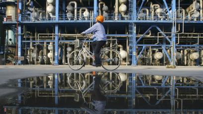 An engineer on a bicycle checks pipelines at a PetroChina's oil refinery in Lanzhou, Gansu province.