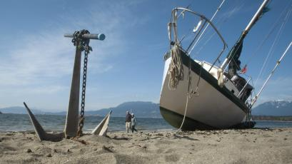 A stranded sailboat's anchor sits in the sand of Kitsilano Beach in Vancouver, British Columbia.