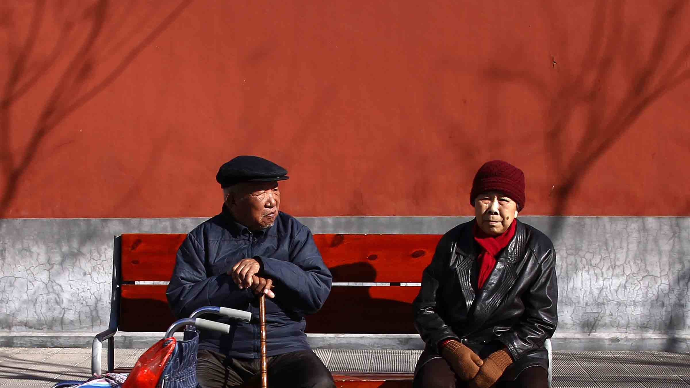 An elderly man with a walking stick sits on a bench next to a woman and a wheelchair in central Beijing