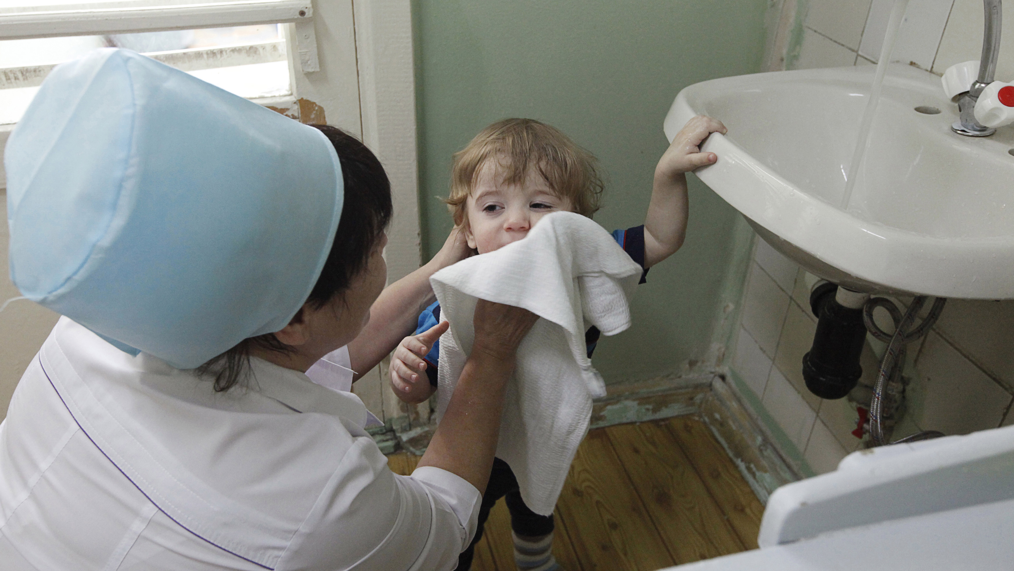 A nurse wipes the face of two-year-old Mark in the children's department of a local hospital in Russia's Siberian city of Krasnoyarsk