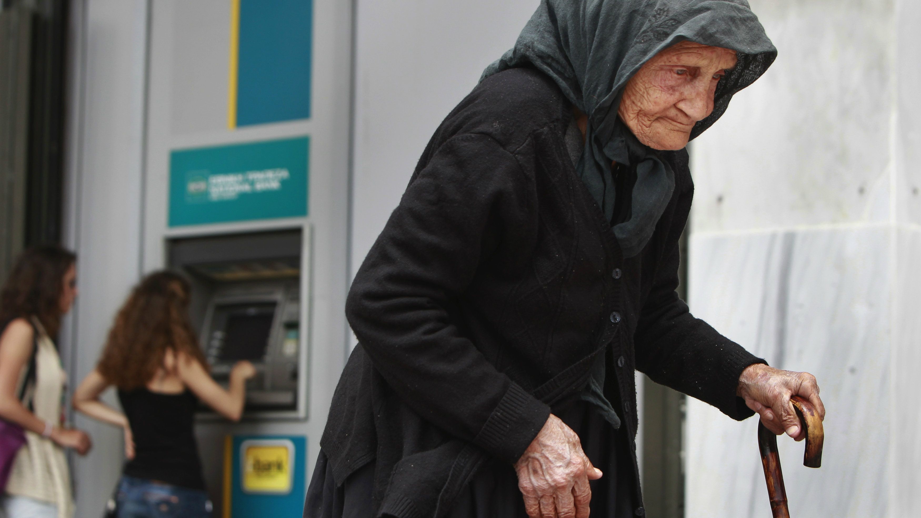 A woman makes her way by as people make a transaction at an ATM machine outside a National Bank branch in central Athens May 29, 2012.
