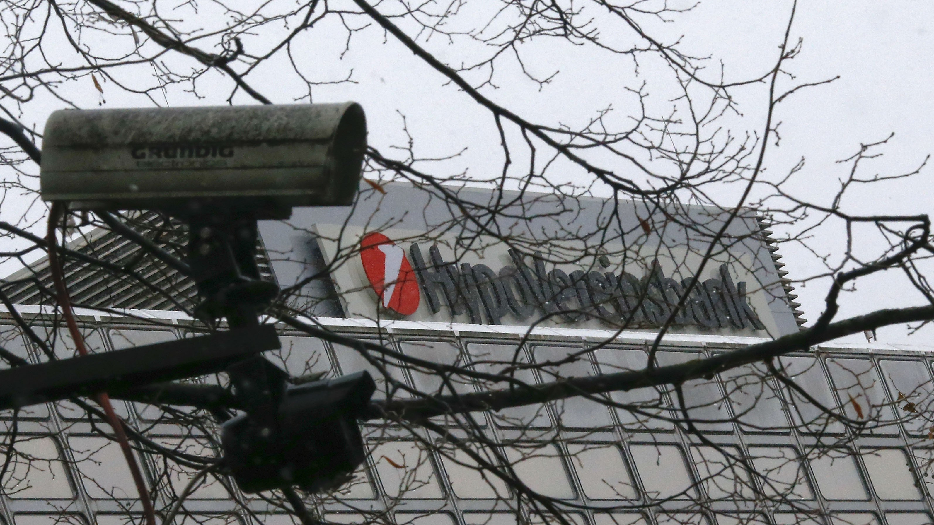 A CCTV camera is pictured next to the logo of UniCredit SpA's German unit HVB (Hypovereinsbank) in Munich November 29, 2012. State prosecutors raided the Munich offices of UniCredit SpA's German unit HVB as part of a tax evasion probe relating to share deals several years ago, HVB said on Thursday.