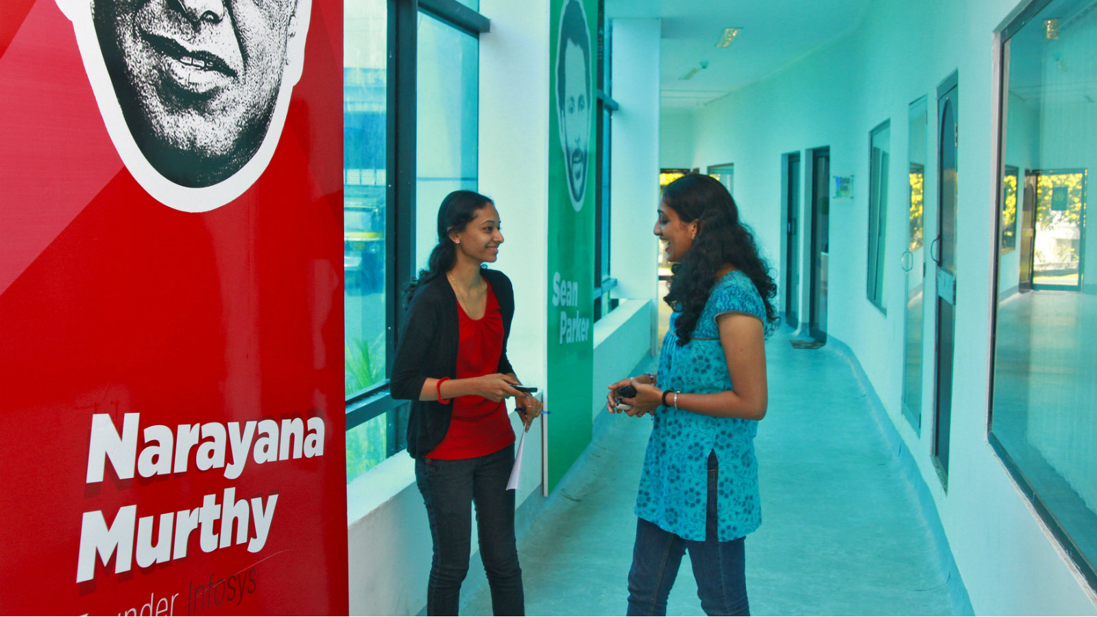 Employees talk as they stand next to flex board poster of Infosys founder Narayana Murthy at the Start-up Village in Kinfra High Tech Park in the southern Indian city of Kochi October 13, 2012. Three decades after Infosys, India's second-largest software service provider, was founded by middle-class engineers, the country has failed to create an enabling environment for first-generation entrepreneurs. Startup Village wants to break the logjam by helping engineers develop 1,000 Internet and mobile companies in the next 10 years. It provides its members with office space, guidance and a chance to hobnob with the stars of the tech industry. But critics say this may not even be the beginning of a game-changer unless India deals with a host of other impediments - from red tape to a lack of innovation and a dearth of investors - that are blocking entrepreneurship in Asia's third-largest economy. To match Feature INDIA-TECHVILLAGE/ Picture taken October 13, 2012.