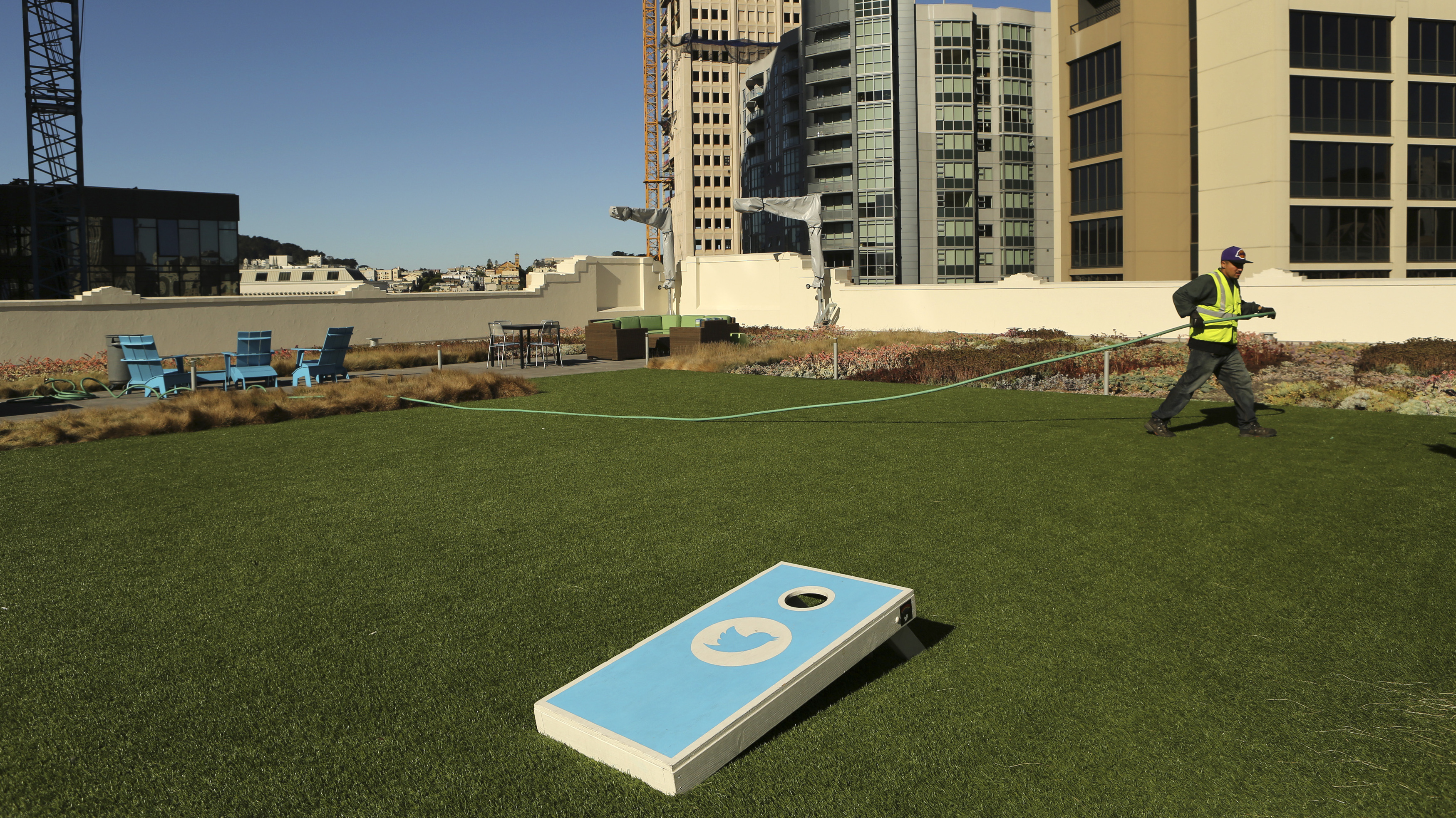 A worker tends to the lawn on the roof of Twitter headquarters in San Francisco, California October 4, 2013. Twitter Inc, racing toward the largest Silicon Valley IPO since Facebook Inc's 2012 coming-out party, hopes to woo investors with rip-roaring revenue growth despite having posted big losses over the past three years. The eight-year-old online messaging service gave potential investors their first glance at its financials on Thursday when it publicly filed its IPO documents, setting the stage for one of the most-anticipated debuts in over a year.   REUTERS/Robert Galbraith  (UNITED STATES - Tags: SCIENCE TECHNOLOGY BUSINESS) - RTR3FLRJ