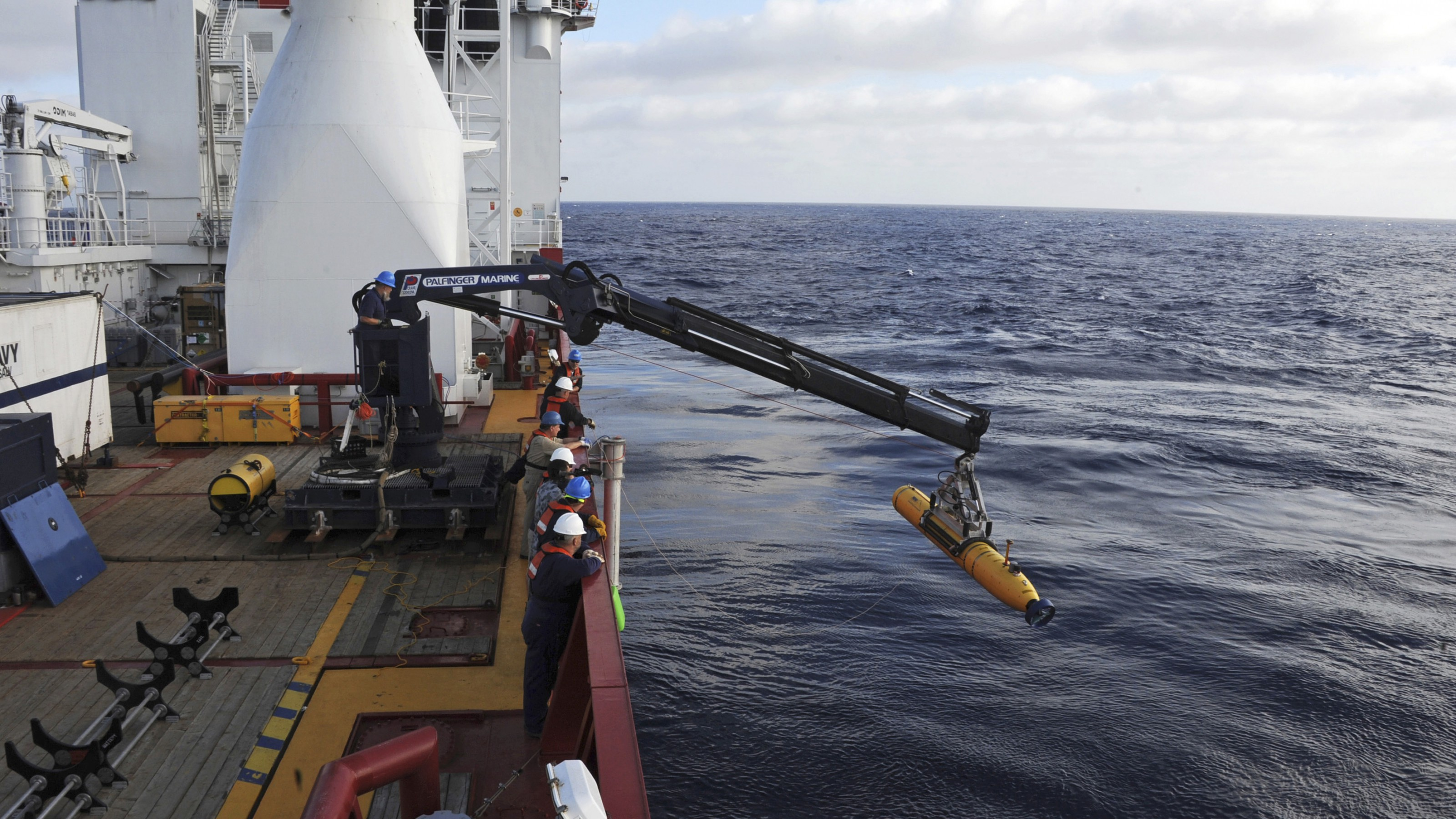 Operators aboard the Australian Defense Vessel Ocean Shield move the U.S. Navy's Bluefin 21 autonomous underwater vehicle into position for deployment in the Southern Indian Ocean, as the search continues for the missing Malaysia Airlines Flight 370, in this handout picture taken April 14, 2014.  Using side scan sonar, the Bluefin will descend to a depth of between 4,000 and 4,500 meters (13,125 to 14,750 feet), approximately 35 meters (115 feet) above the ocean floor, according to a U.S. Navy news release. Picture taken April 14, 2014.  REUTERS/U.S. Navy/Mass Communication Specialist 1st Class Peter D. Blair/Handout via Reuters (MID-SEA - Tags: MILITARY DISASTER) ATTENTION EDITORS - THIS IMAGE WAS PROVIDED BY A THIRD PARTY. FOR EDITORIAL USE ONLY. NOT FOR SALE FOR MARKETING OR ADVERTISING CAMPAIGNS. THIS PICTURE IS DISTRIBUTED EXACTLY AS RECEIVED BY REUTERS, AS A SERVICE TO CLIENTS - RTR3LEUS