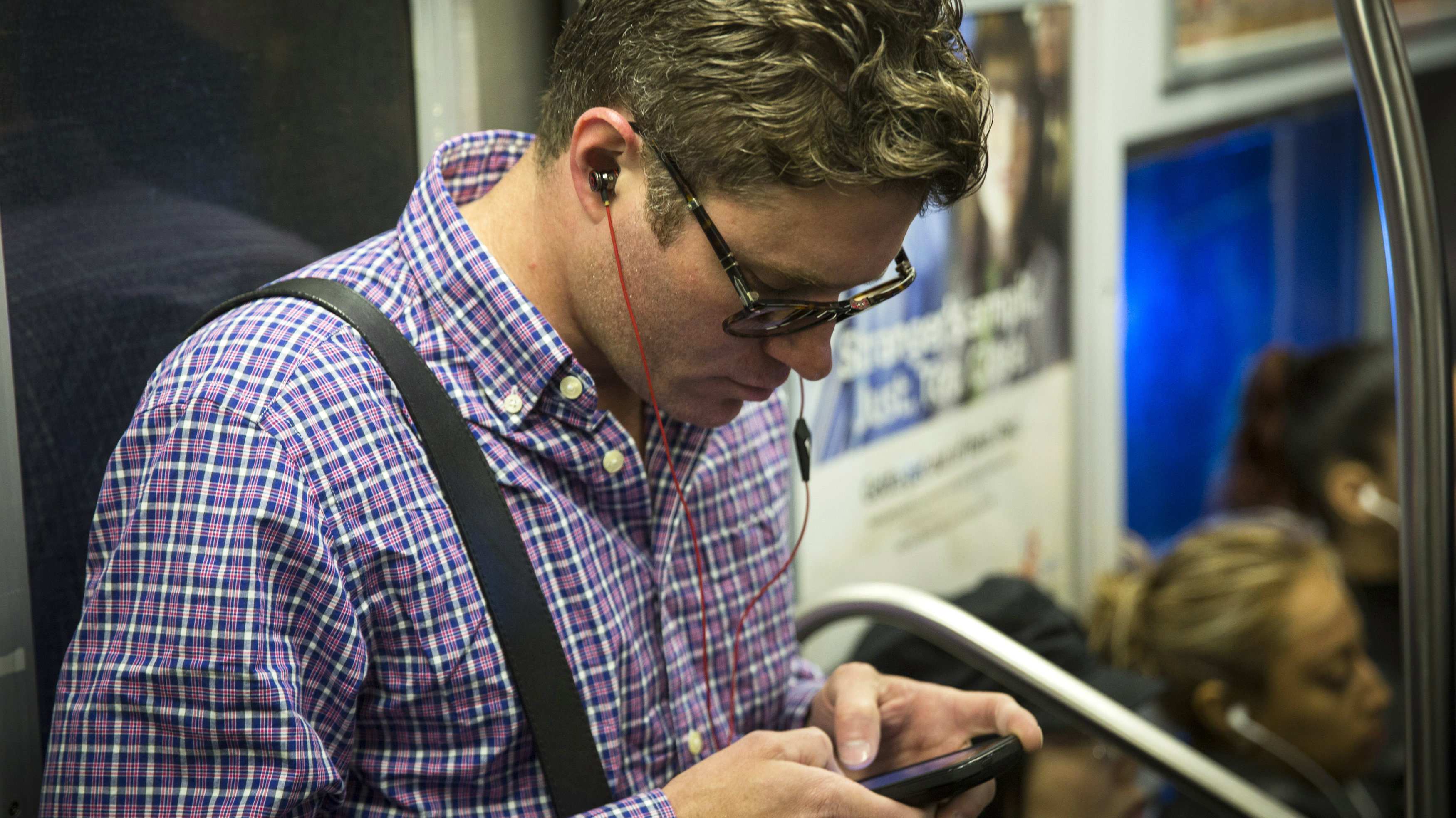 A commuter listens to Beats brand headphones while riding the subway in New York.