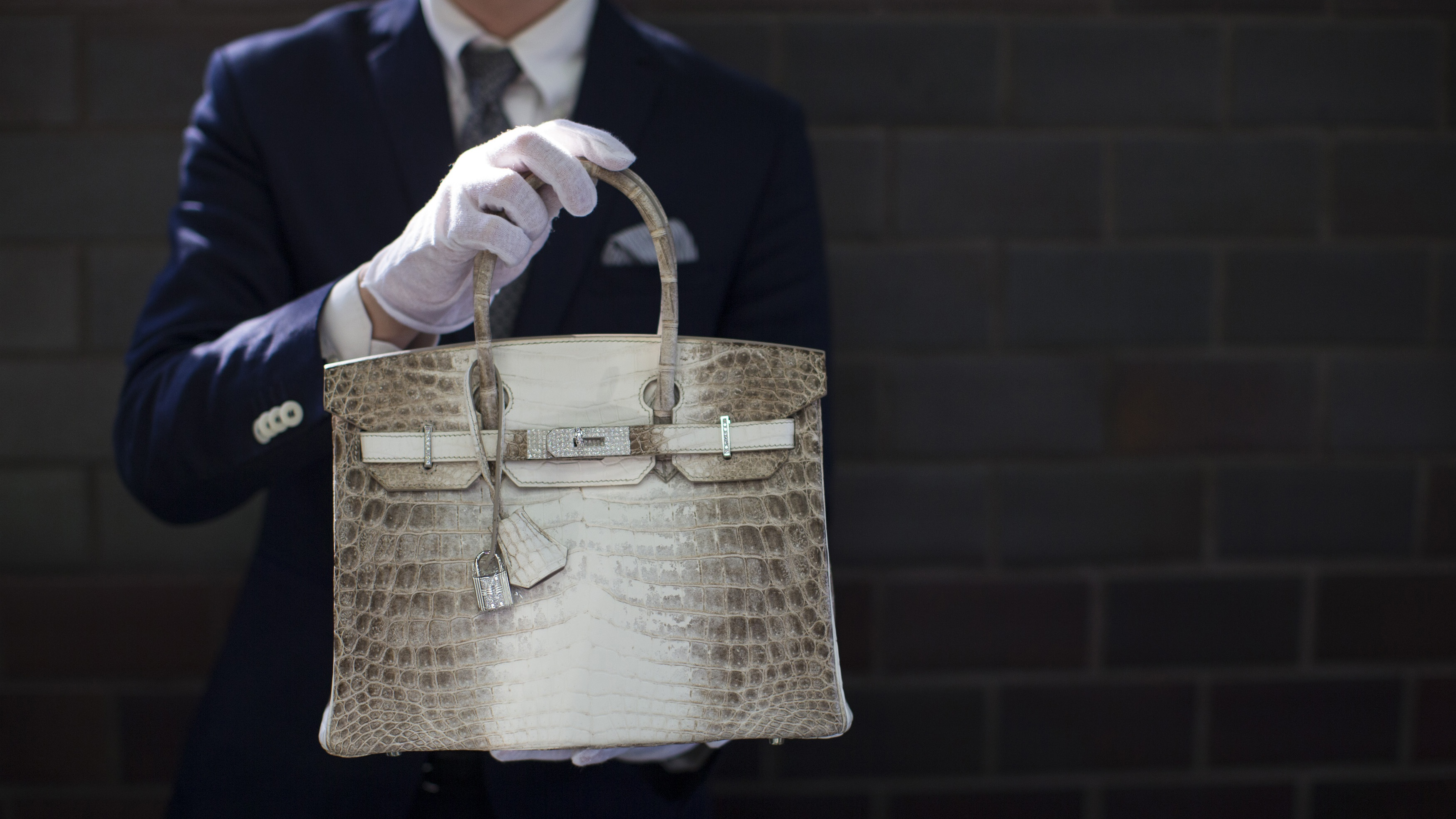 An employee holds an Hermes diamond and Himalayan Nilo Crocodile Birkin handbag at Heritage Auctions offices in Beverly Hills, California September 22, 2014. The handbag has 242 diamonds with a total of 9.84 carats.