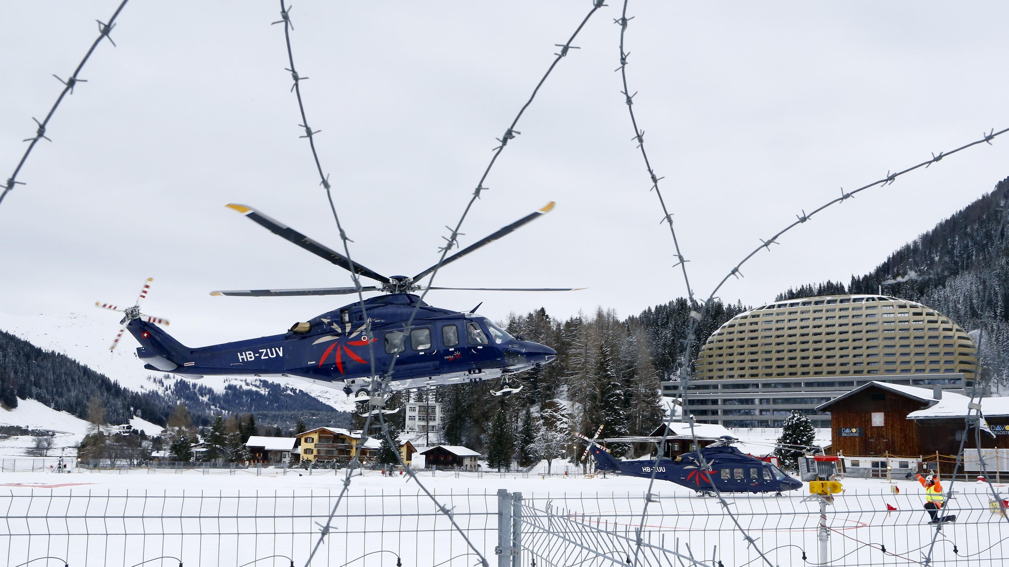 A participant arrives by private helicopter for the World Economic Forum (WEF)  in the Swiss mountain resort of Davos January 20, 2015. More than 1,500 business leaders and 40 heads of state or government will attend the January 21-24 meeting of the World Economic Forum (WEF) to network and discuss big themes, from the price of oil to the future of the Internet. This year they are meeting in the midst of upheaval, with security forces on heightened alert after attacks in Paris, the European Central Bank considering a radical government bond-buying programme and the safe-haven Swiss franc rocketing.