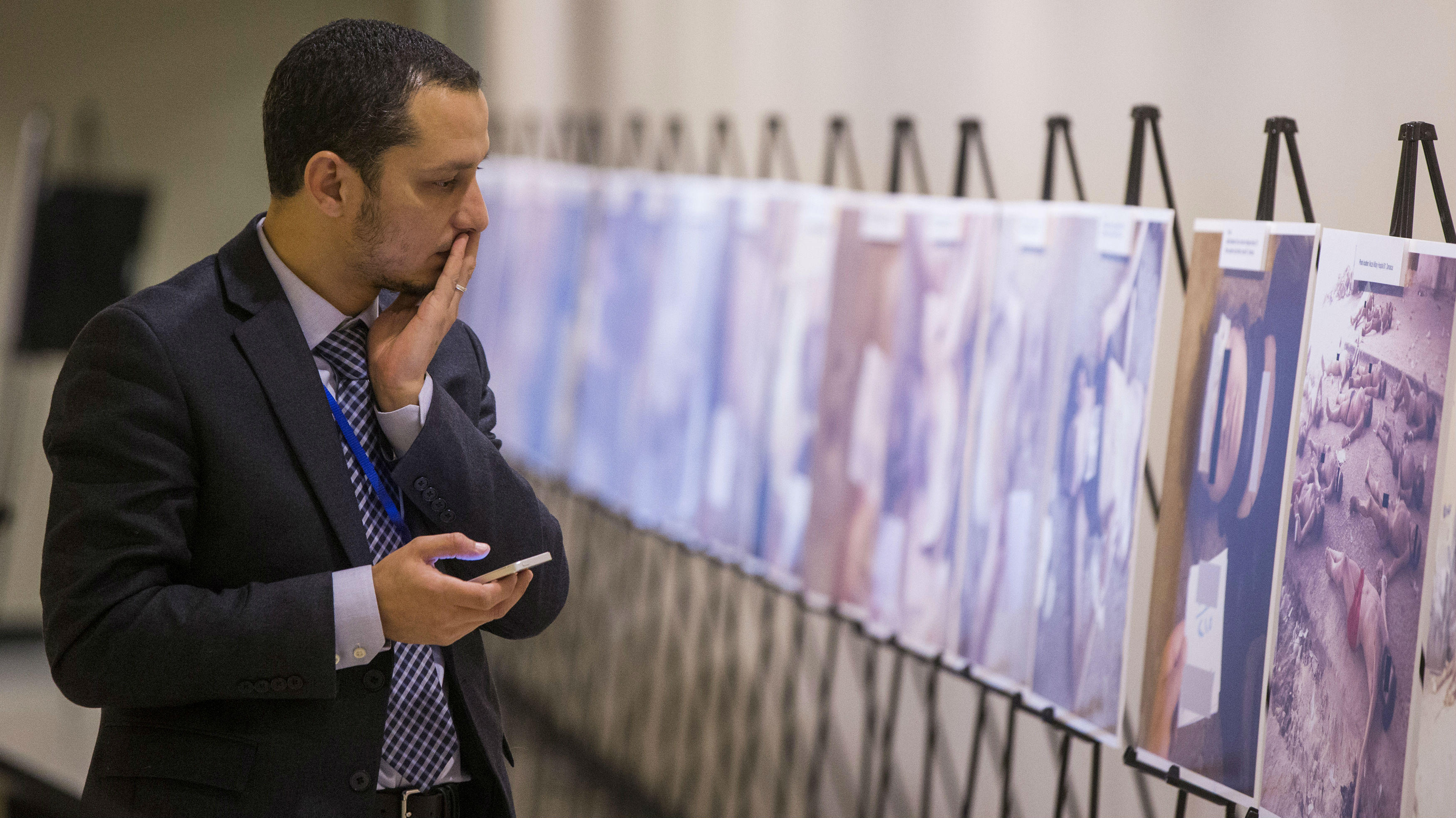 """A man reacts as he looks at a gruesome collection of images of dead bodies taken by a photographer, who has been identified by the code name """"Caesar,"""" at the United Nations Headquarters in New York, March 10, 2015. The pictures were smuggled out of Syria between 2011 and mid-2013. The exhibition at the UN consists of two dozen images selected from the roughly 55,000 photographs taken in Syria by a former military police photographer - some showing eye gougings, strangulation and long-term starvation - as the conflict in Syria enters its fifth year. REUTERS/Lucas Jackson (UNITED STATES - Tags: POLITICS CIVIL UNREST CONFLICT) TEMPLATE OUT"""