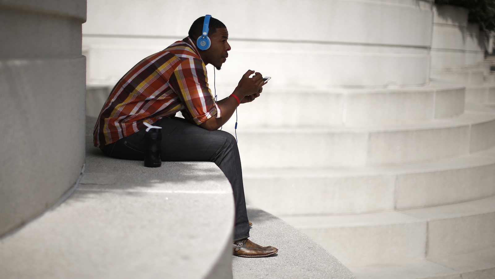 A man with Beats headphones listens to music on an iPhone in Los Angeles, California March 10, 2015.   REUTERS/Lucy Nicholson (UNITED STATES - Tags: SOCIETY) - RTR4SUFC