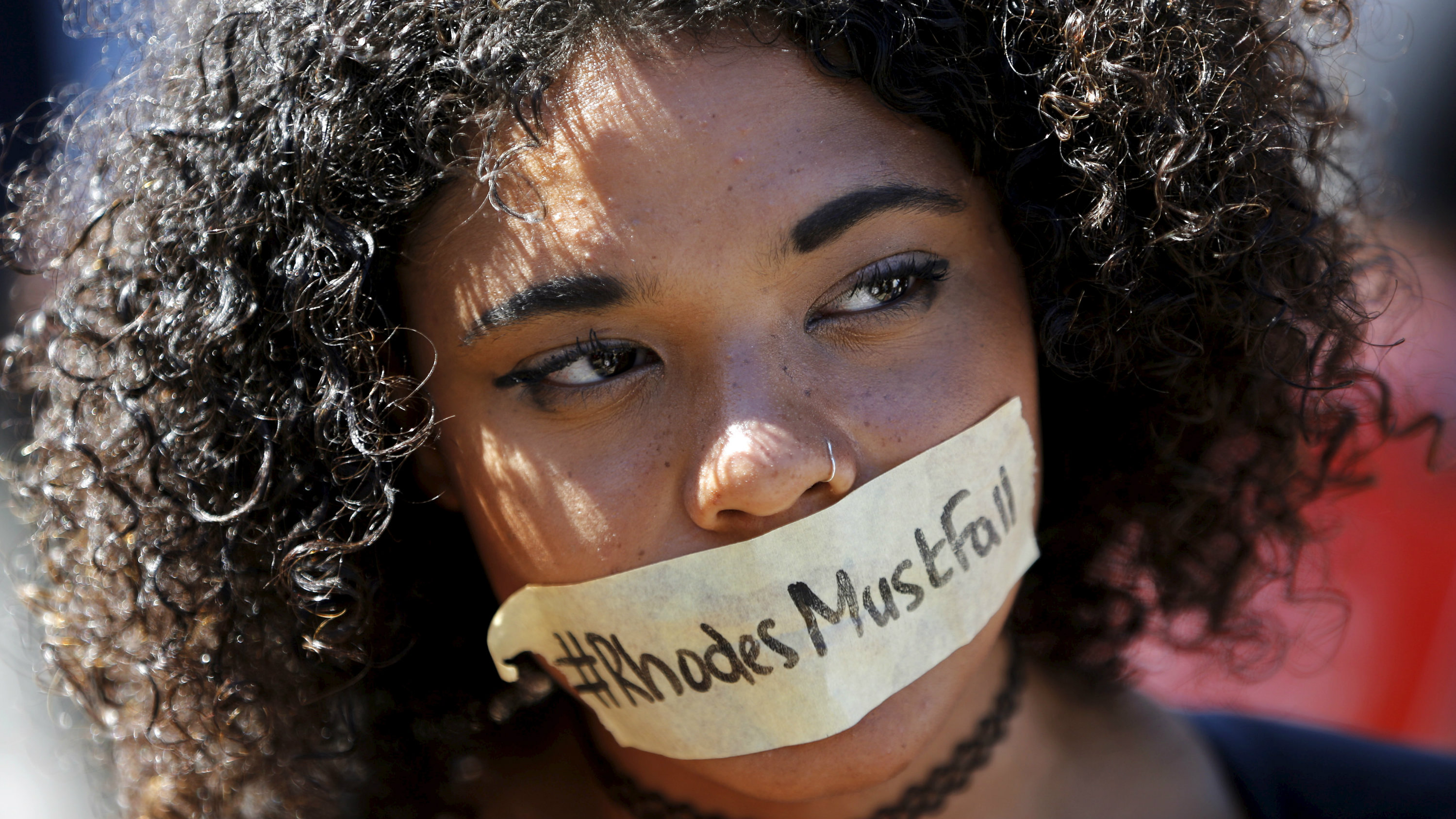 A student with a #RhodesMustFall sticker taped across her mouth.