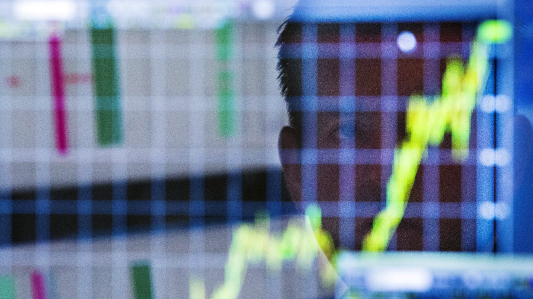 A trader looks up at a chart on his computer screen while working on the floor of the New York Stock Exchange.