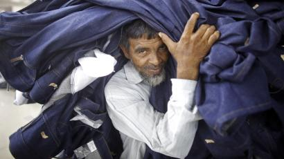 A worker carries a stack of clothes in a garment factory in Bangladesh.