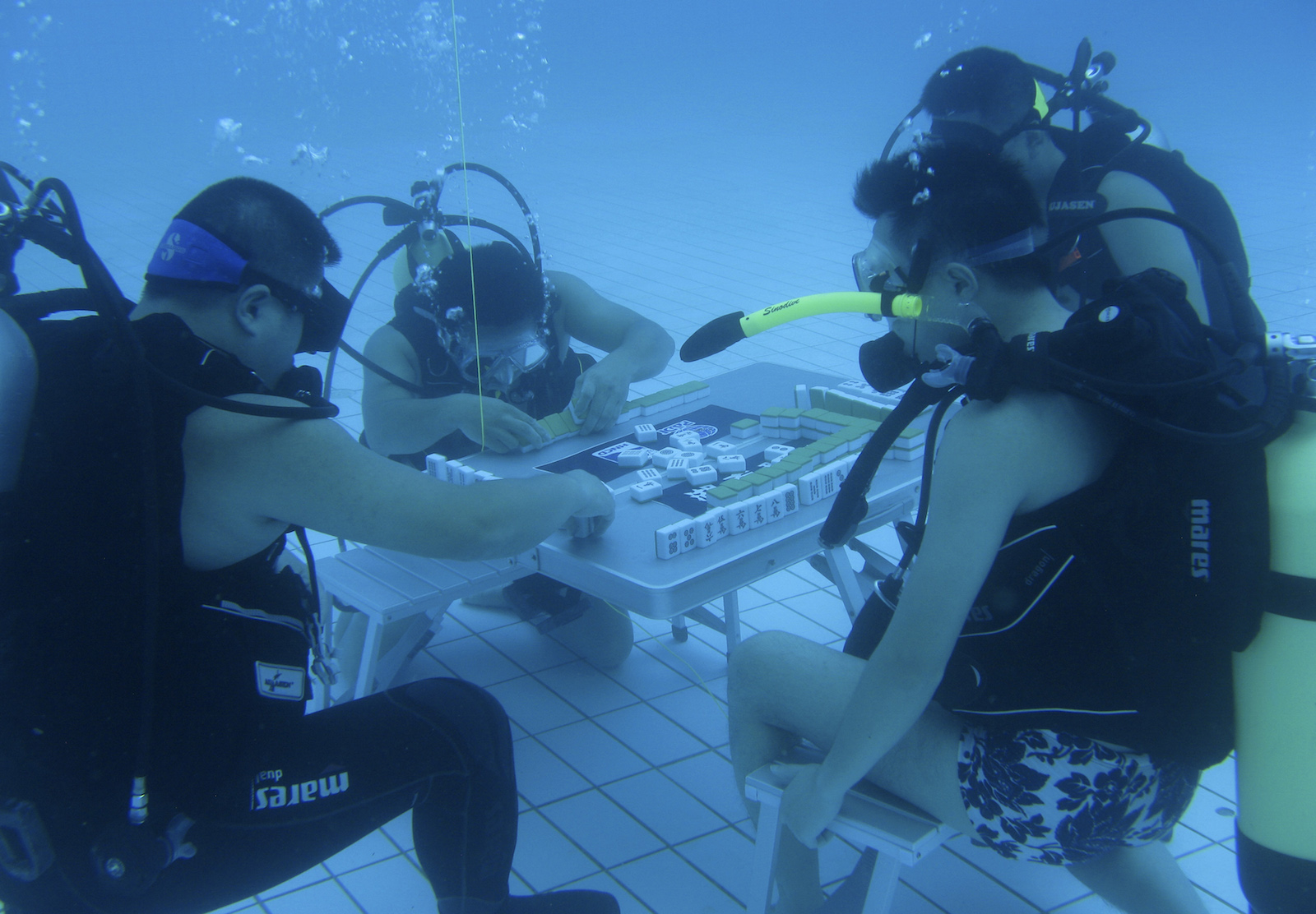 Diving instructors play mahjong in a swimming pool in Xiangtan, Hunan province August 9, 2013. According to local media, the trainers re-invented the game of mahjong by playing it under water in a 5.5-metre-deep pool to escape from the summer heat, and since then more than 10 divers have been playing the game. China's top meteorological authority on Tuesday continued to warn of prolonged heat that has afflicted central and eastern China since July, Xinhua News Agency reported. Picture taken August 9, 2013.