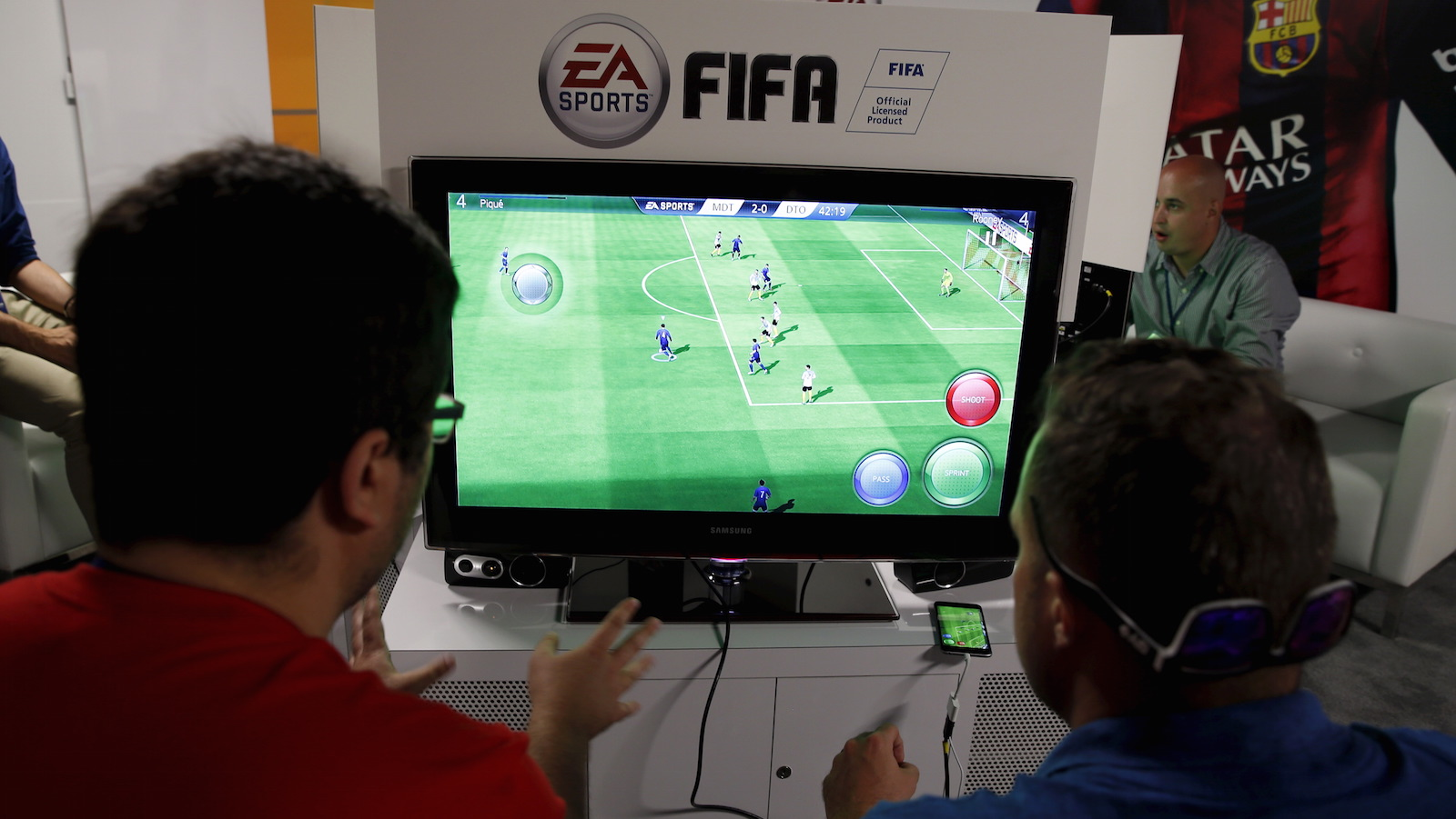 """People play Electronic Arts' """"FIFA"""" video game at the Microsoft Xbox booth at the Electronic Entertainment Expo, or E3, in Los Angeles, California, United States, June 16, 2015. REUTERS/Lucy Nicholson  - RTX1GT4J"""