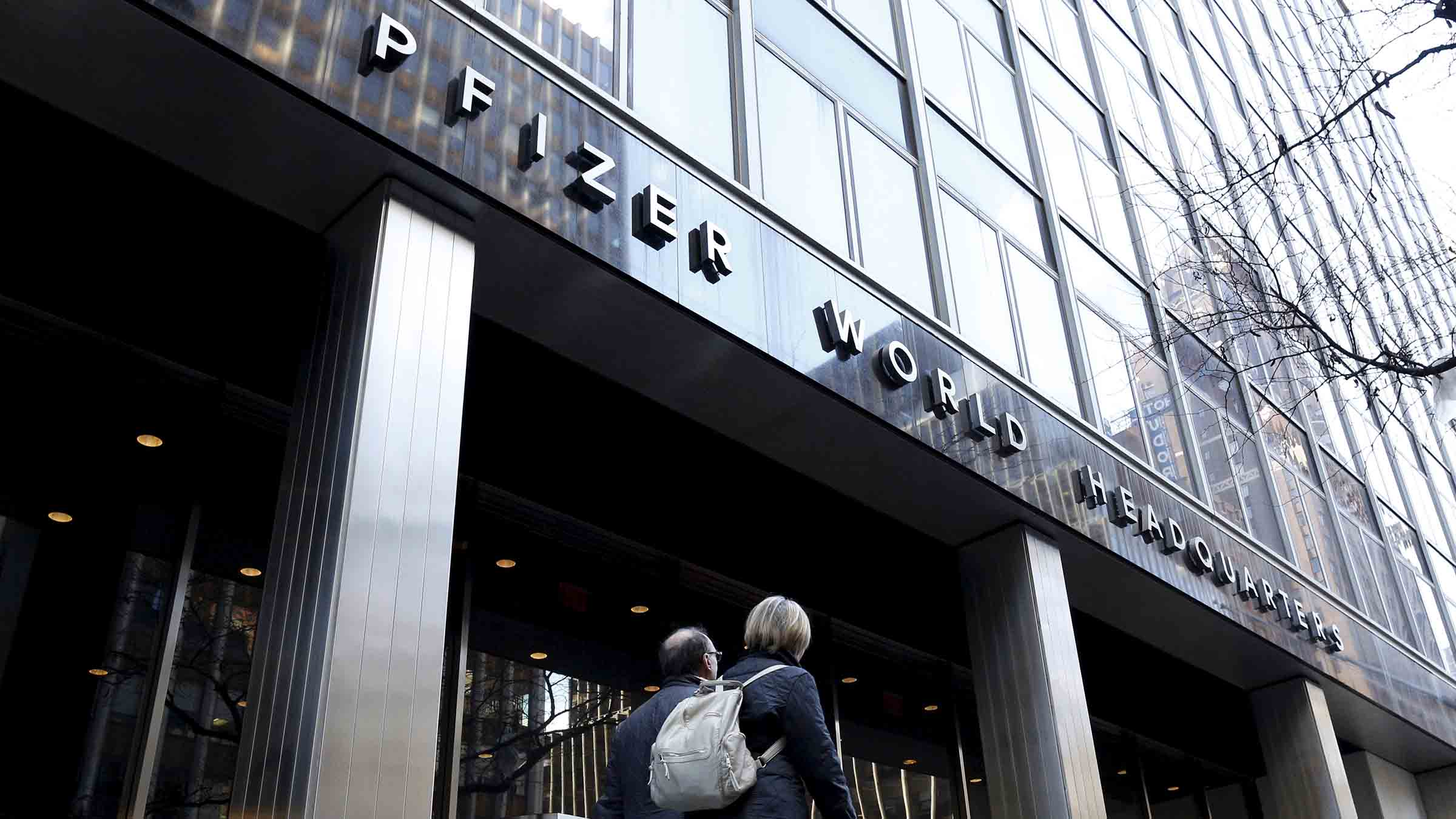 People pass by the Pfizer World Headquarters building in New York