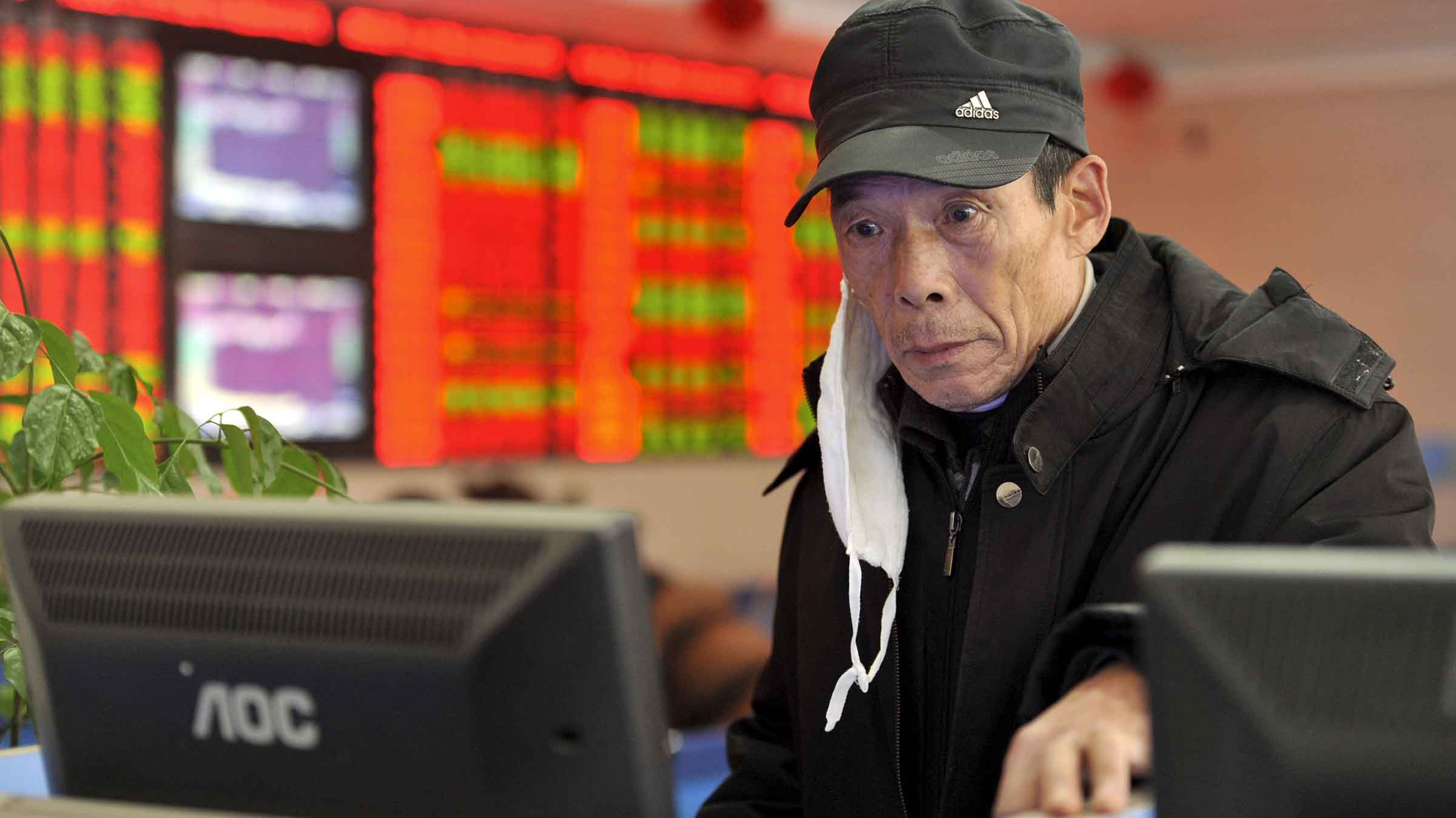 An investor with a face mask looks at a computer screen showing stock information at a brokerage house in Fuyang