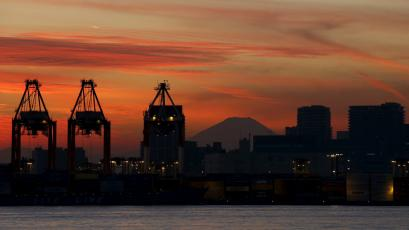 Mt. Fuji is seen between cranes and buildings during sunset at a port in Tokyo.