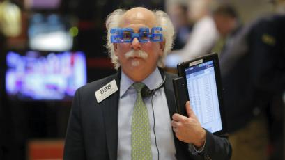 Trader Peter Tuchman wears plastic glasses to celebrate the last trading day of 2015 as he works on the floor of the New York Stock Exchange.
