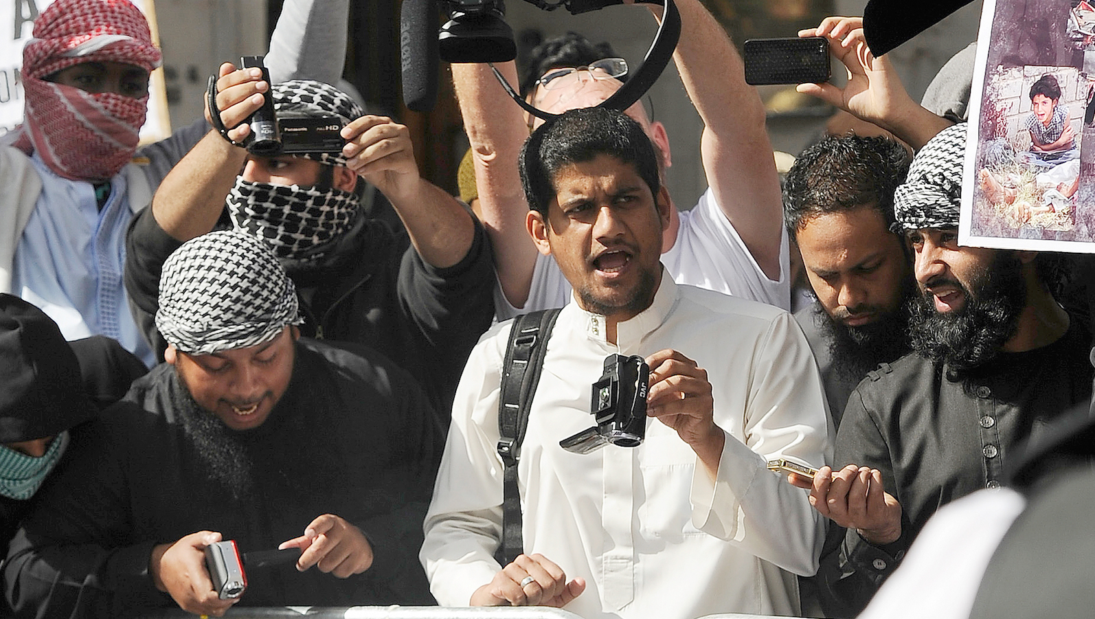 A file picture shows a man identified by local media as Siddharta Dhar (C in white) as he takes part in a demonstration outside the U.S. embassy in central London, September 11, 2011. Dhar is widely identified by local media as the masked figure with a British accent in the latest video distributed by ISIS which shows the execution of 5 men.     TPX IMAGES OF THE DAY - RTX213O1