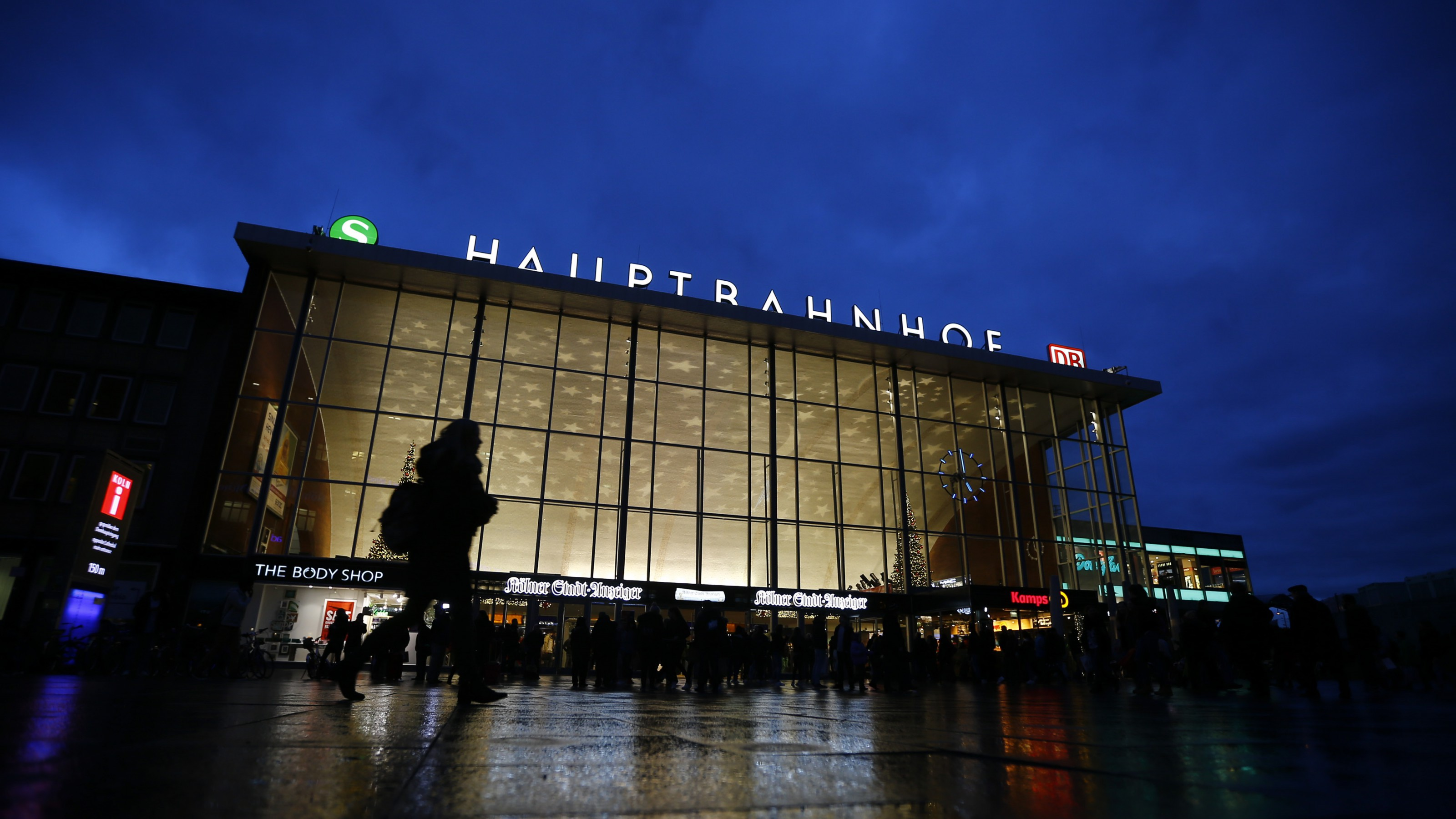 People are silhouetted as they walk past the main railway station in Cologne, Germany, January 5, 2016. About 90 women have reported being robbed, threatened or sexually molested at the New Year's celebrations outside Cologne's cathedral by young, mostly drunk, men, police said on Tuesday. One woman said she was raped. Police and witnesses have said about 1,000 men, split into groups, attacked women in the square. Some witnesses said the men were of North African appearance, stirring strong emotions in Germany where Chancellor Angela Merkel has welcomed people fleeing war zones in the Middle East and Africa.   REUTERS/Wolfgang Rattay  - RTX214SE