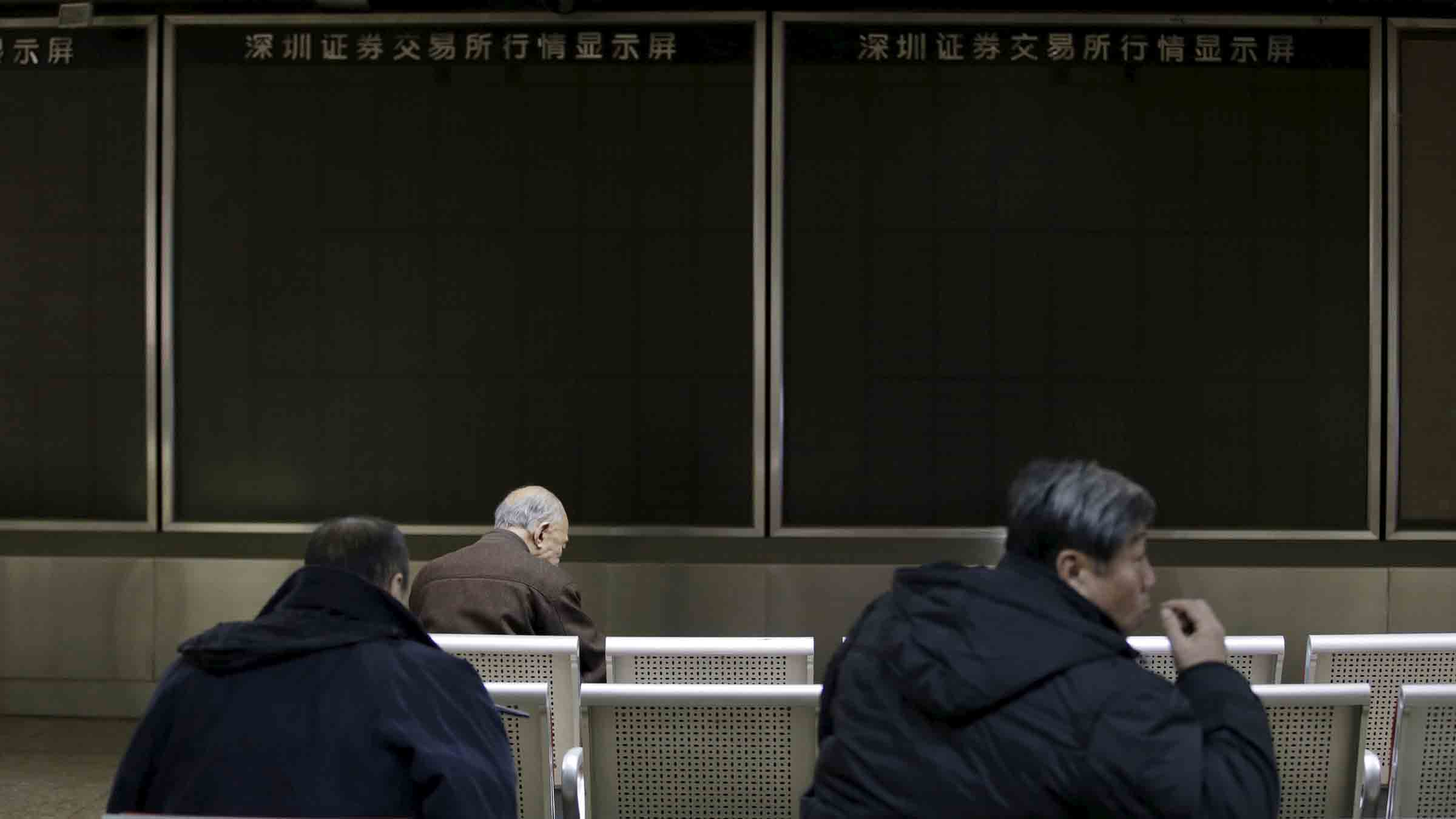 People sit in front of an electronic boarding that was turned off after trading was suspended, in Beijing