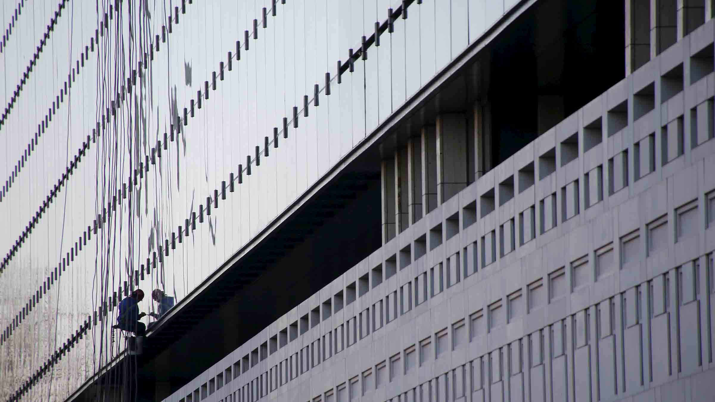 A window cleaner works on exterior of a building of a state-run bank in  Beijing