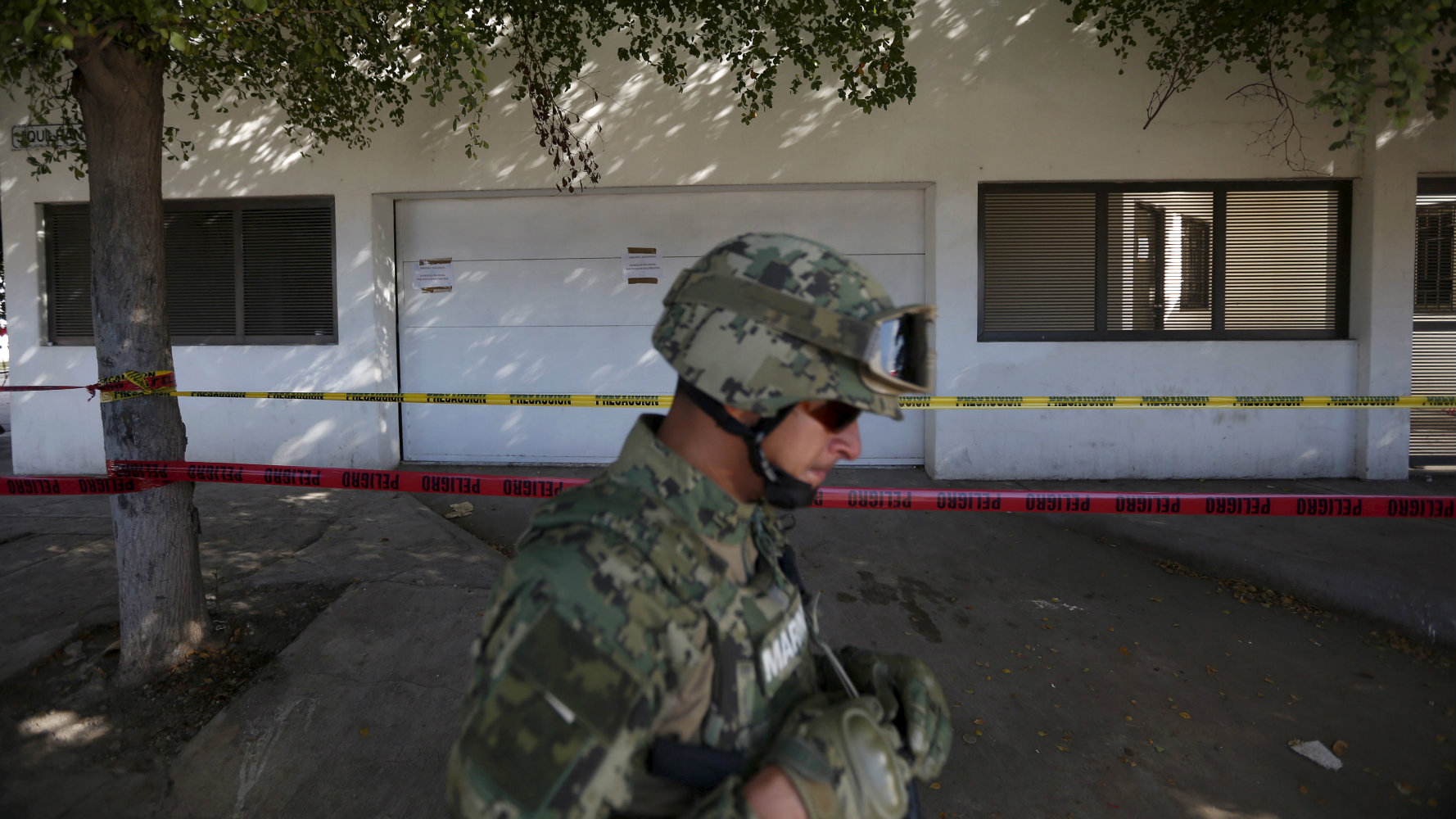 "A soldier keeps watch outside the house where five people were shot dead during an operation to recapture the world's top drug lord Joaquin ""El Chapo"" Guzman."