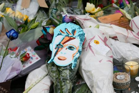 """Flowers and tributes lie at a mural of David Bowie in Brixton, south London, January 11, 2016. David Bowie, a music legend who used daringly androgynous displays of sexuality and glittering costumes to frame legendary rock hits """"Ziggy Stardust"""" and """"Space Oddity"""", has died of cancer."""
