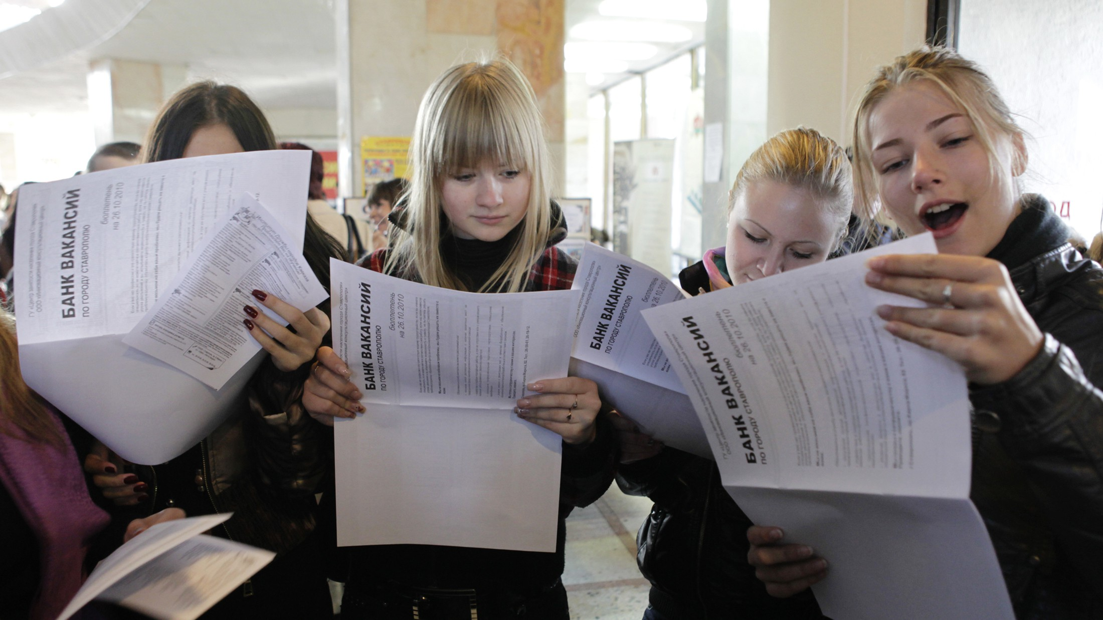 Women look at job listings during the 22nd city job fair held in Russia's southern city of Stavropol October 26, 2010.