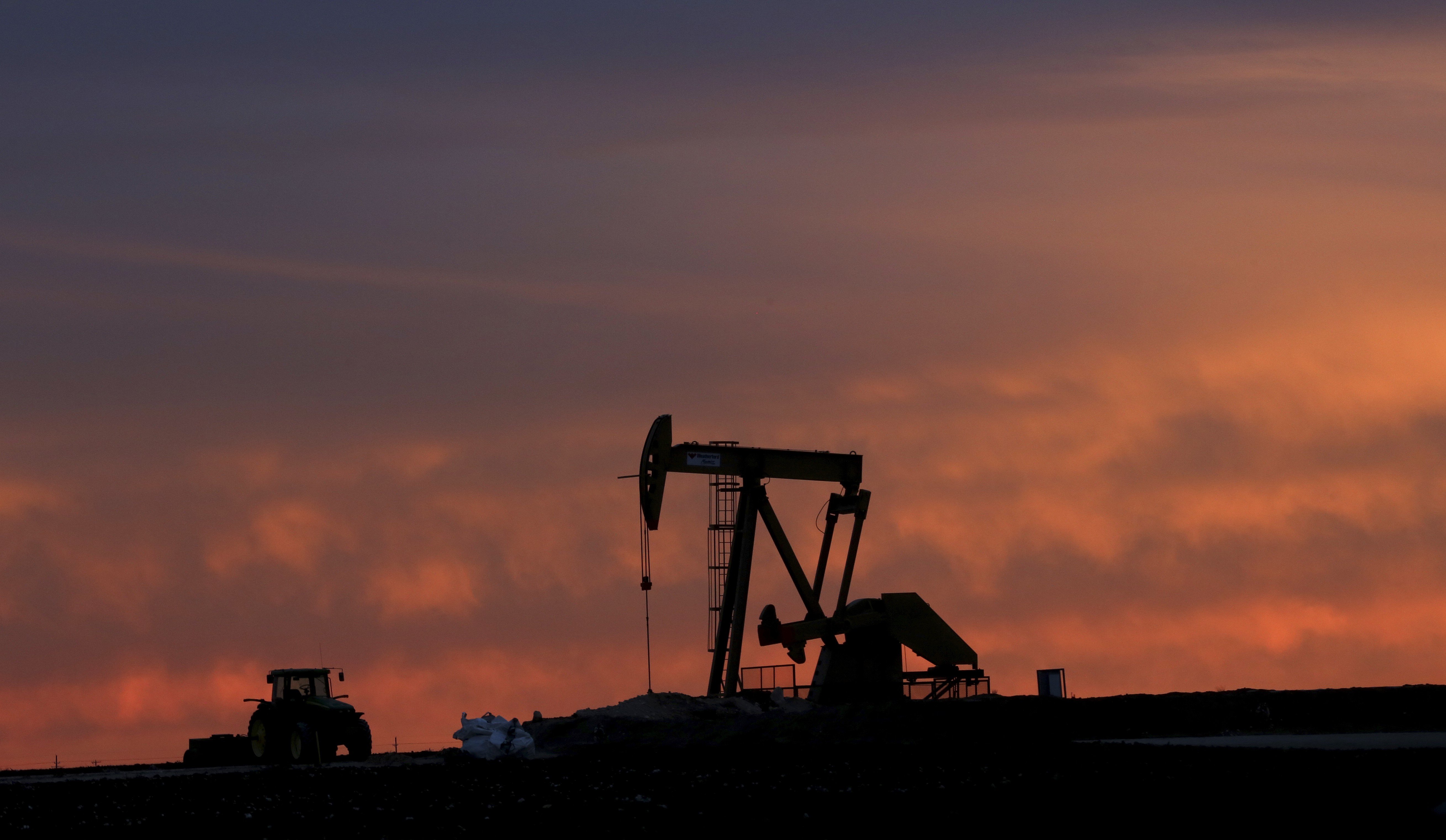 In this photo made Monday, Dec. 22, 2014, a well pump works at sunset on a farm near Sweetwater, Texas. At the heart of the Cline, a shale formation once thought to hold more oil than Saudi Arabia, Sweetwater is bracing for layoffs and budget cuts, anxious as oil prices fall and its largest investors pull back.