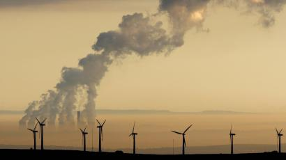 Steam rises from a power station behind the Royd Moor Wind Farm in Penistone near Sheffield