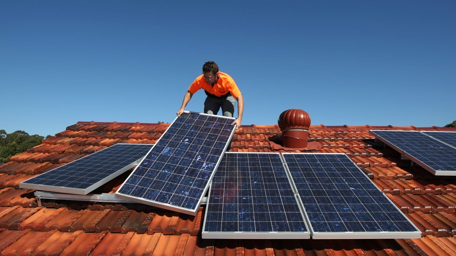 Solar system installer Thomas Bywater adjusts new solar panels.