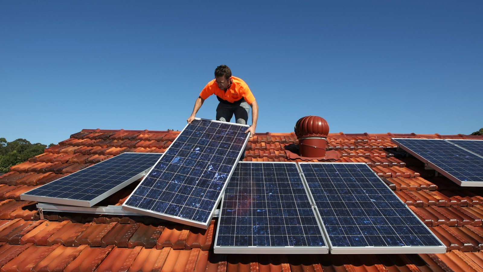 Solar system installer Thomas Bywater adjusts new solar panels.