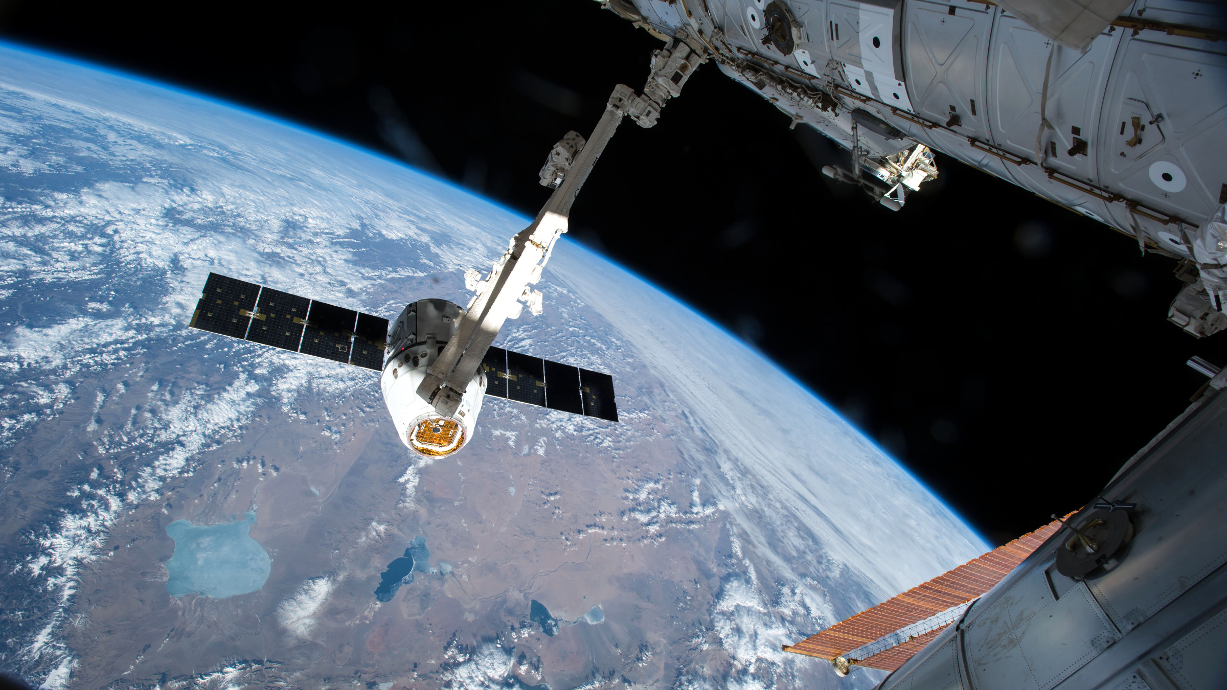 The Canadarm 2 reaches out to capture the SpaceX Dragon cargo spacecraft and prepare it to be pulled into its port on the International Space Station Friday April 17, 2015. The Canadarm2 robotic arm will maneuver Dragon to its installation position at the Earth-facing port of the Harmony module where it will reside for the next five weeks.