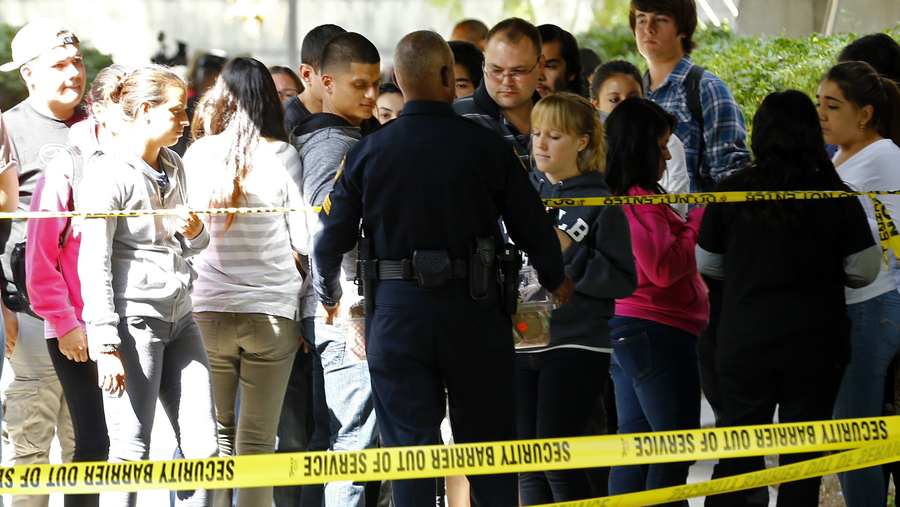 Students line up for food after being cordoned off by police and barrier tape due to an Ebola scare at Southwestern College in Chula Vista, California October 16, 2014. The abundance of caution had officials keeping students from leaving a section of the school after one of them reported her sister became sick after returning from a trip. The school later released a statement saying the student's family had travelled to the Midwest, and that a nurse had examined the student and found no symptoms resembling Ebola. REUTERS/Mike Blake