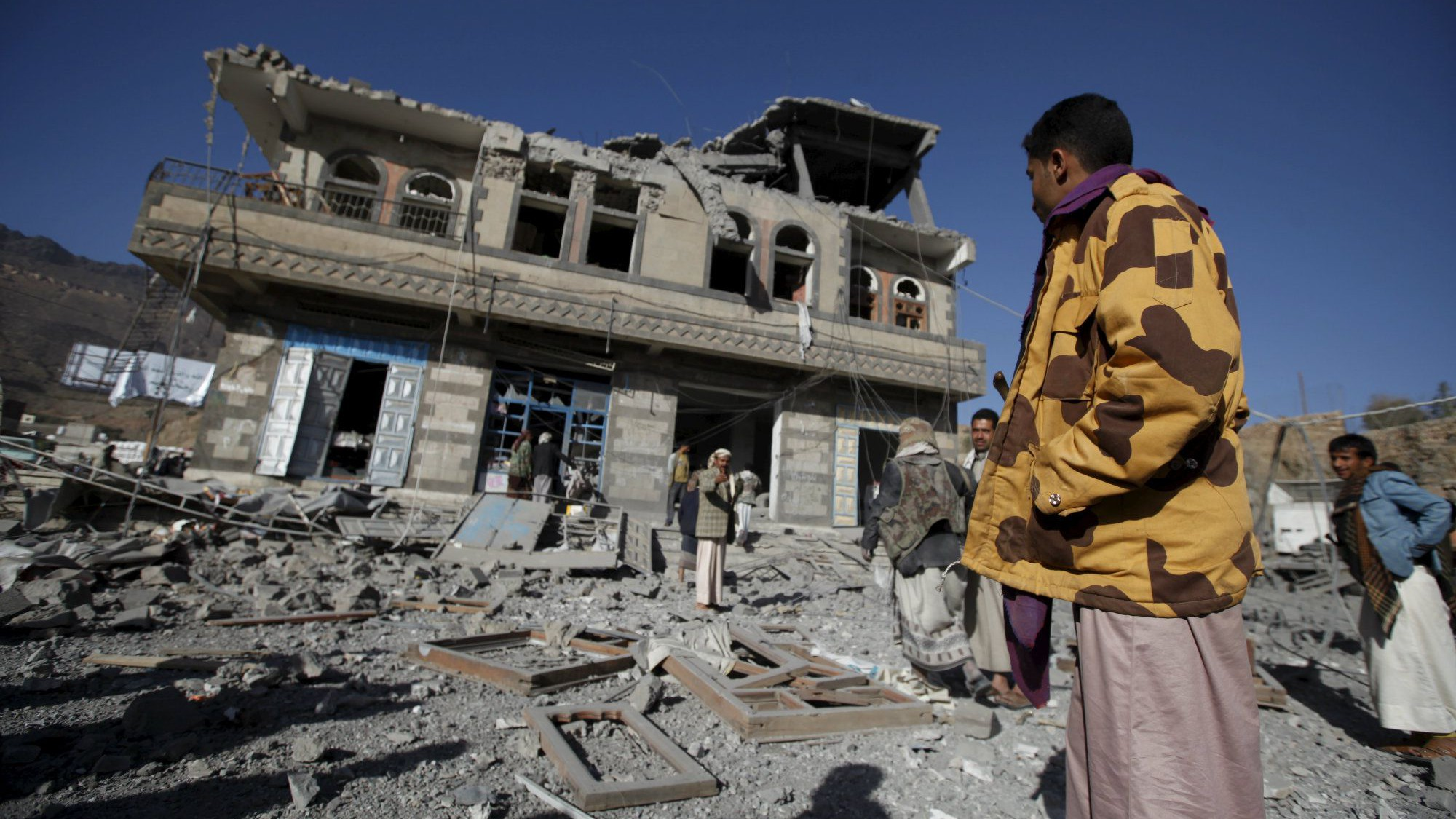 People look at a damaged building at the site of a Saudi-led air strike in Yemen's capital Sanaa January 4, 2016.