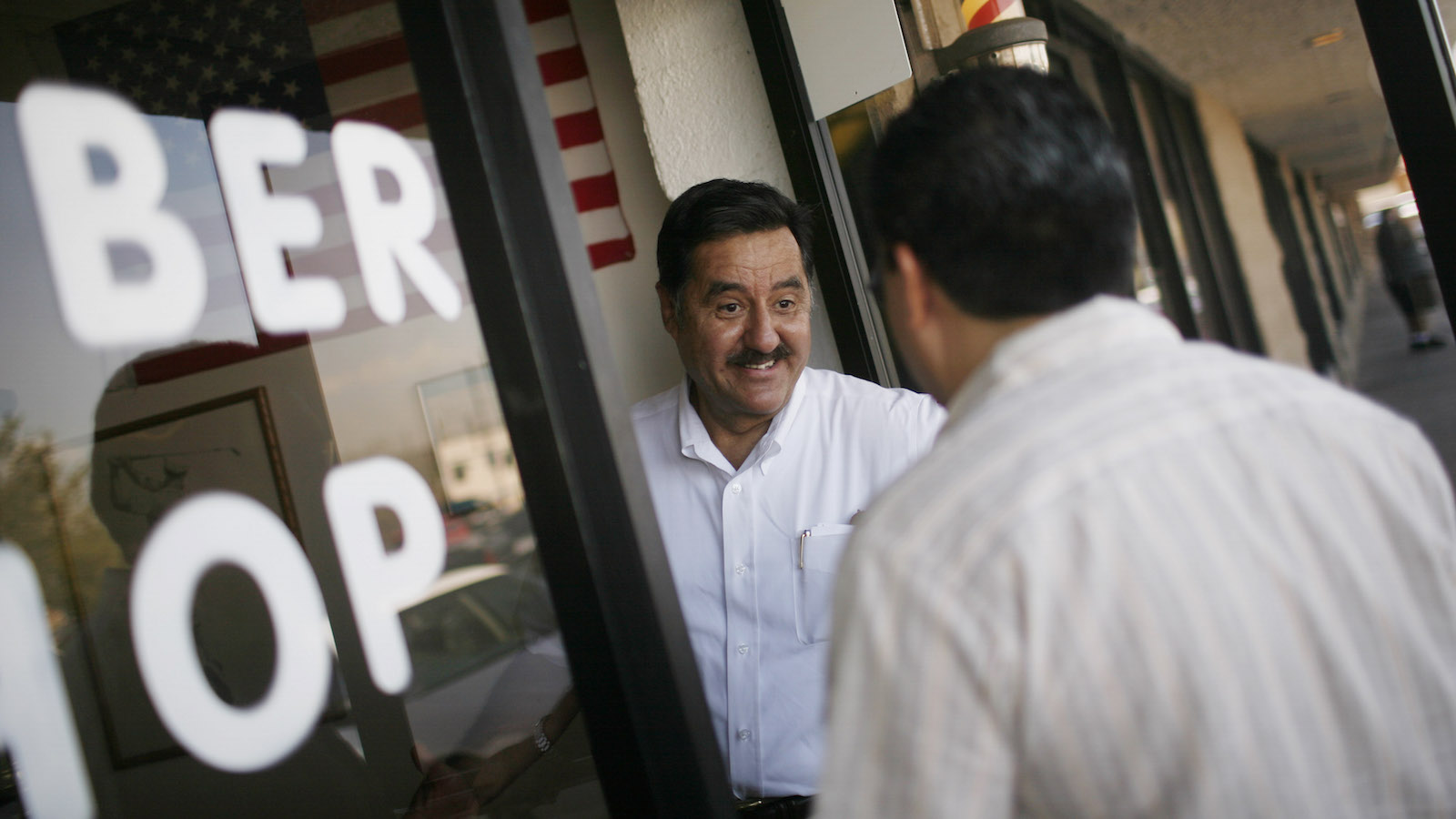 Xavier Rivas, a Republican activist working on Sen. John McCain's Nevada Leadership Team, visits a barbershop in Henderson, Nev., Friday, Sept. 26, 2008. The man who once risked his career on an immigration reform bill that was embraced by Hispanics is now struggling to win these same voters, and falling perilously below the level of support that helped lift President Bush to the White House. The candidate who won nearly 70 percent of Hispanic voters in his last bid for Senate in border-state Arizona is watching a first-term Illinois senator run away with those voters. (AP Photo/Jae C. Hong)