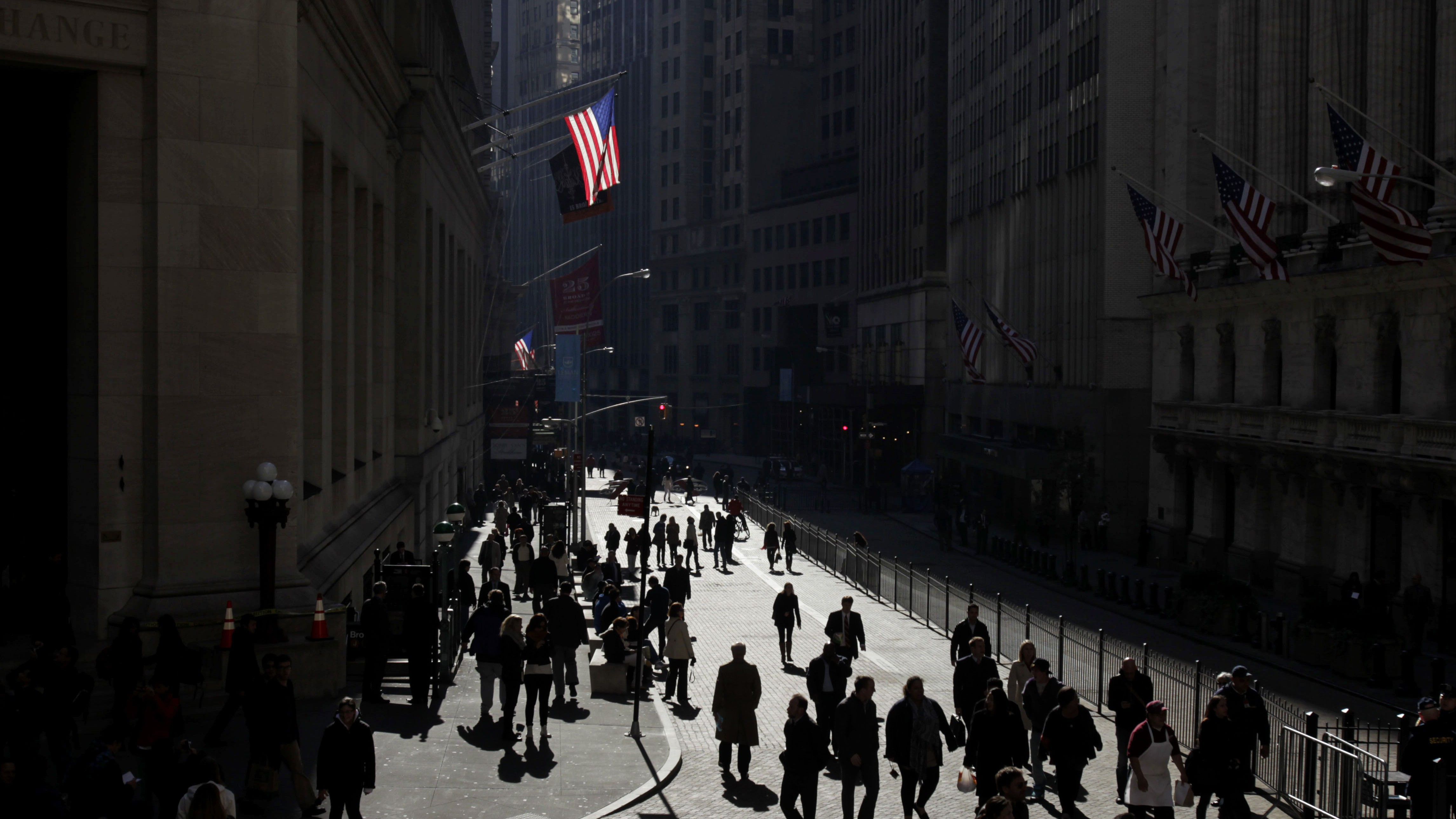 People walk freely in front of the New York Stock Exchange, which had been blocked by barricades since the start of the Occupy Wall Street protests in New York, Wednesday, Nov. 2, 2011. ()