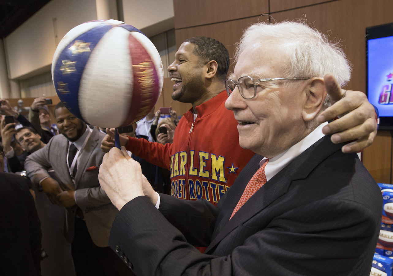 "Berkshire Hathaway Chairman and CEO Warren Buffett, right, is watched by Detroit Lions defensive tackle Ndamukong Suh, left, as he is assisted by Harlem Globetrotter Chris ""Handles"" Franklin in spinning a basketball in Omaha, Neb., Saturday, May 4, 2013, before holding the Berkshire Hathaway shareholders meeting. Tens of thousands attend Berkshire Hathaway shareholder meeting to hear Warren Buffett and Charlie Munger answer questions for more than six hours. No other annual meeting can rival Berkshire's, which is known for its size, the straight talk Buffett and Munger offer and the sales records shareholders set while buying Berkshire products."
