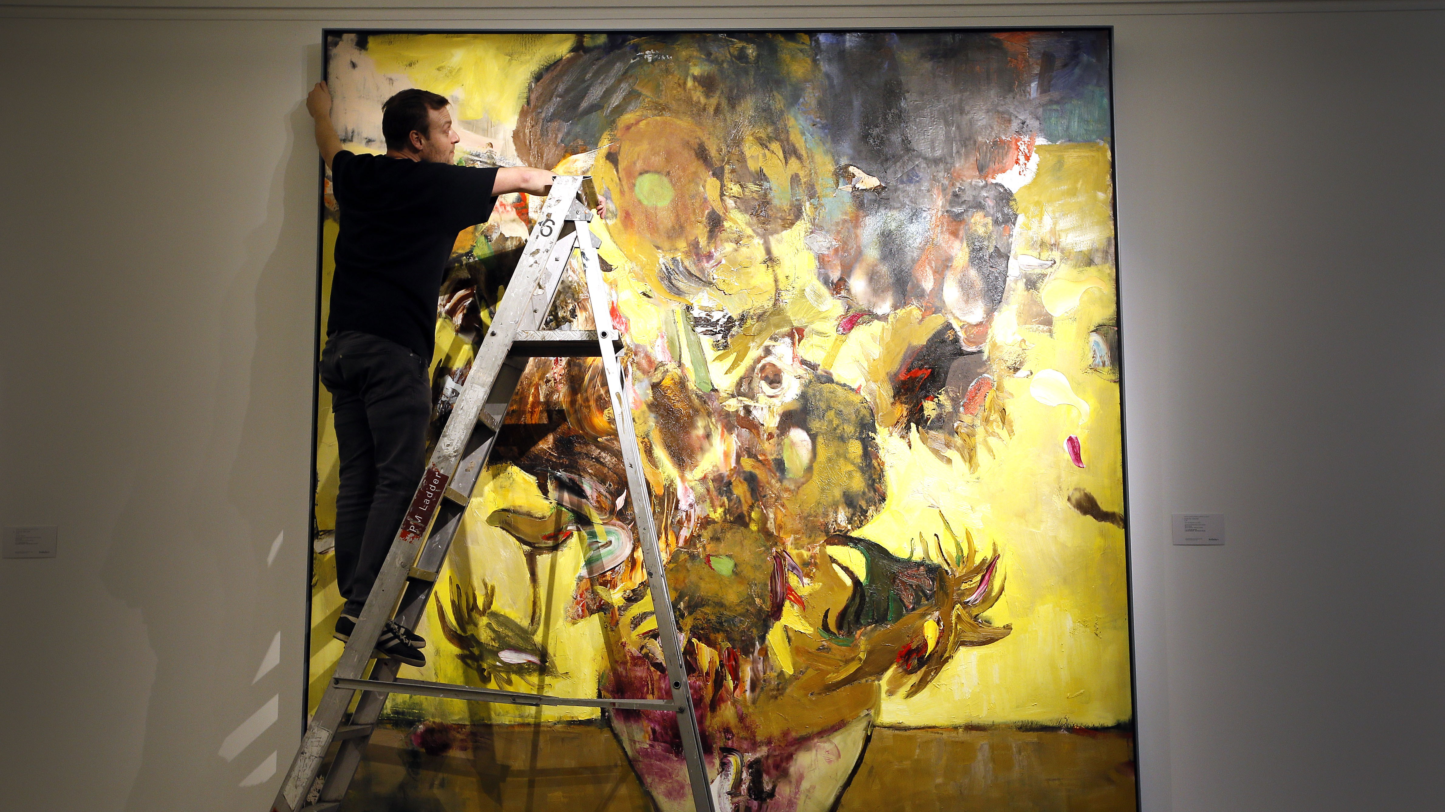 A Sotheby's employee adjusts a painting by Adrien Ghenie called 'The Sunflowers in 1937' at the auction rooms in London, Thursday, Jan. 28, 2016. The painting is estimated at 400,000-600,000 UK pounds (572,000-858,000 US dollars) when it goes up for auction in London on Feb.10 in the Contemporary Art Evening Sale.