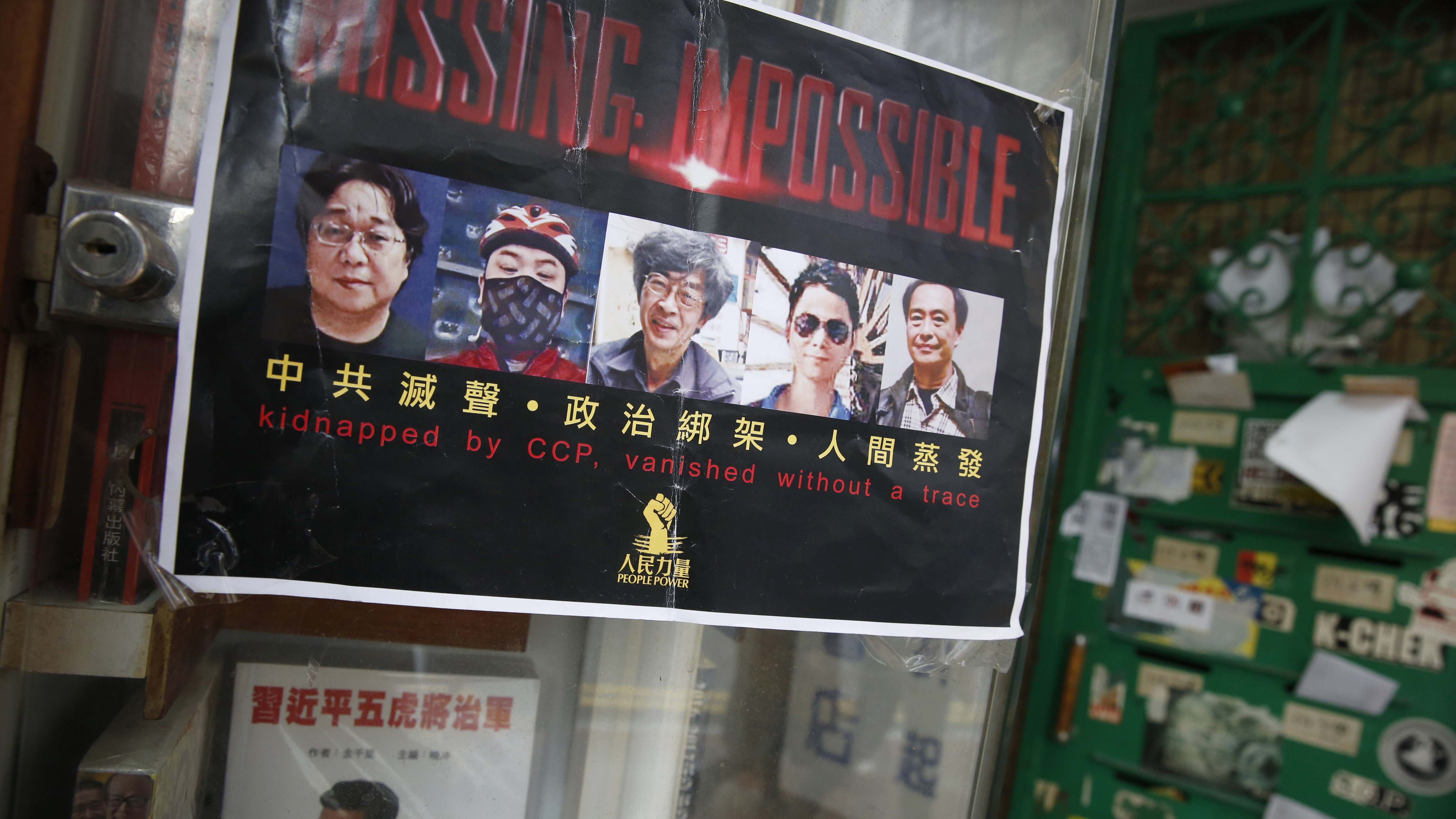 A poster featuring five missing Hong Kong booksellers is displayed by their supporters at the entrance of the closed Causeway Bay Bookstore which is known for gossipy titles about Chinese political scandals and other sensitive issues that are popular with visiting tourists from the mainland, in Hong Kong, Friday, Feb. 5, 2016. Mainland Chinese authorities say they're investigating three missing Hong Kong booksellers for unspecified criminal activity, shedding more light on a case that's gripped residents with fear that Beijing is tightening its hold on the city. (AP Photo/Kin Cheung)