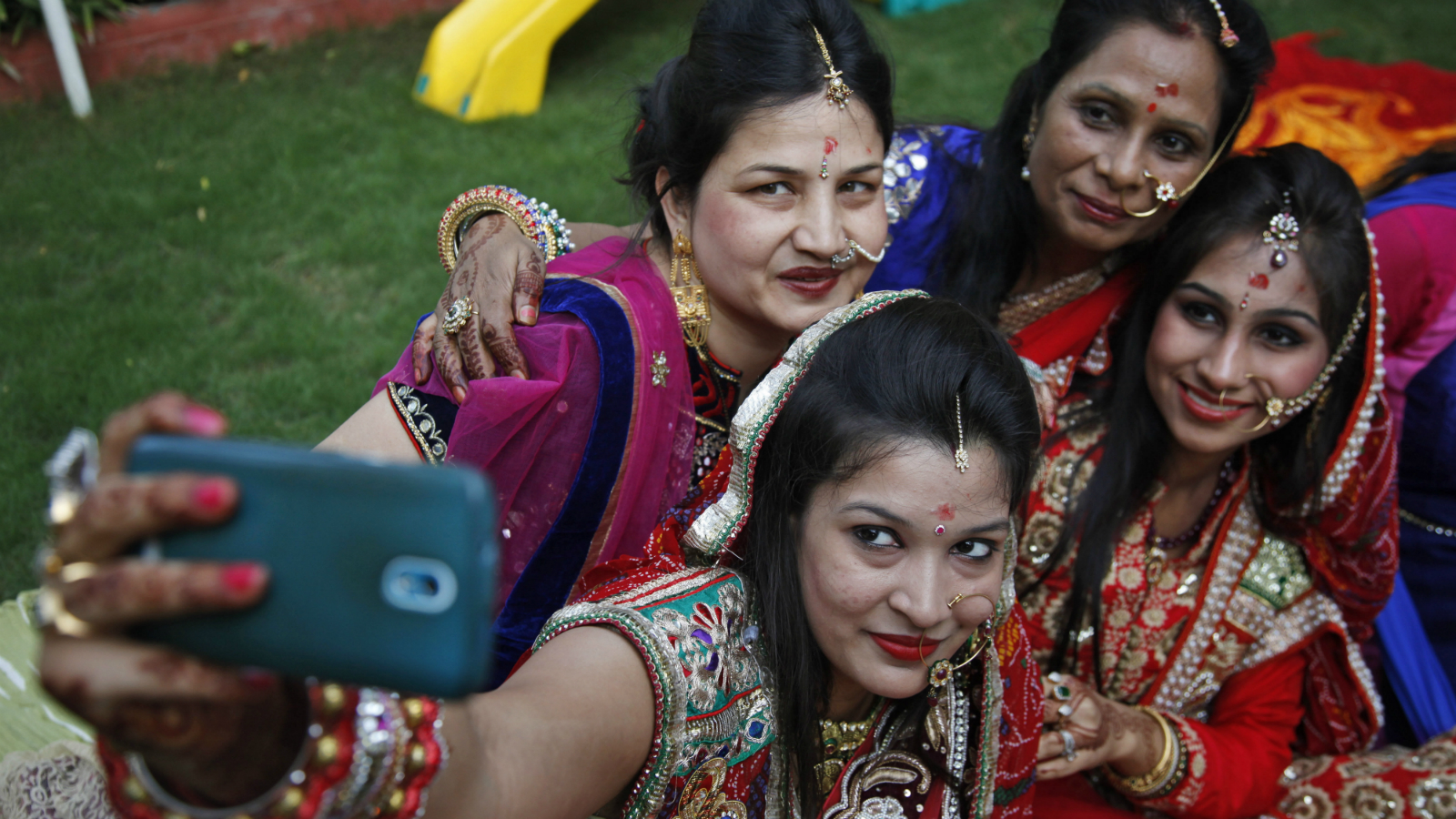Indian Hindu married women take a selfie from a mobile phone after performing rituals on Karva Chauth festival in Ahmadabad, India, Friday, Oct. 30, 2015. Married women decorate their hands with henna on Karva Chauth festival and observe a fast to pray for the longevity and well being of their husbands.